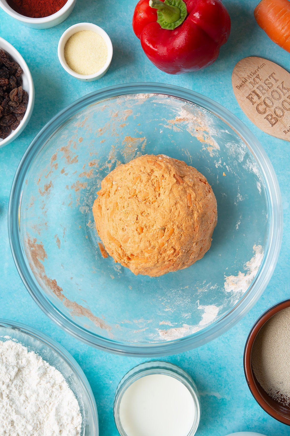 Paprika and carrot bread dough in a mixing bowl. Ingredients to make bread snakes surround the bowl.