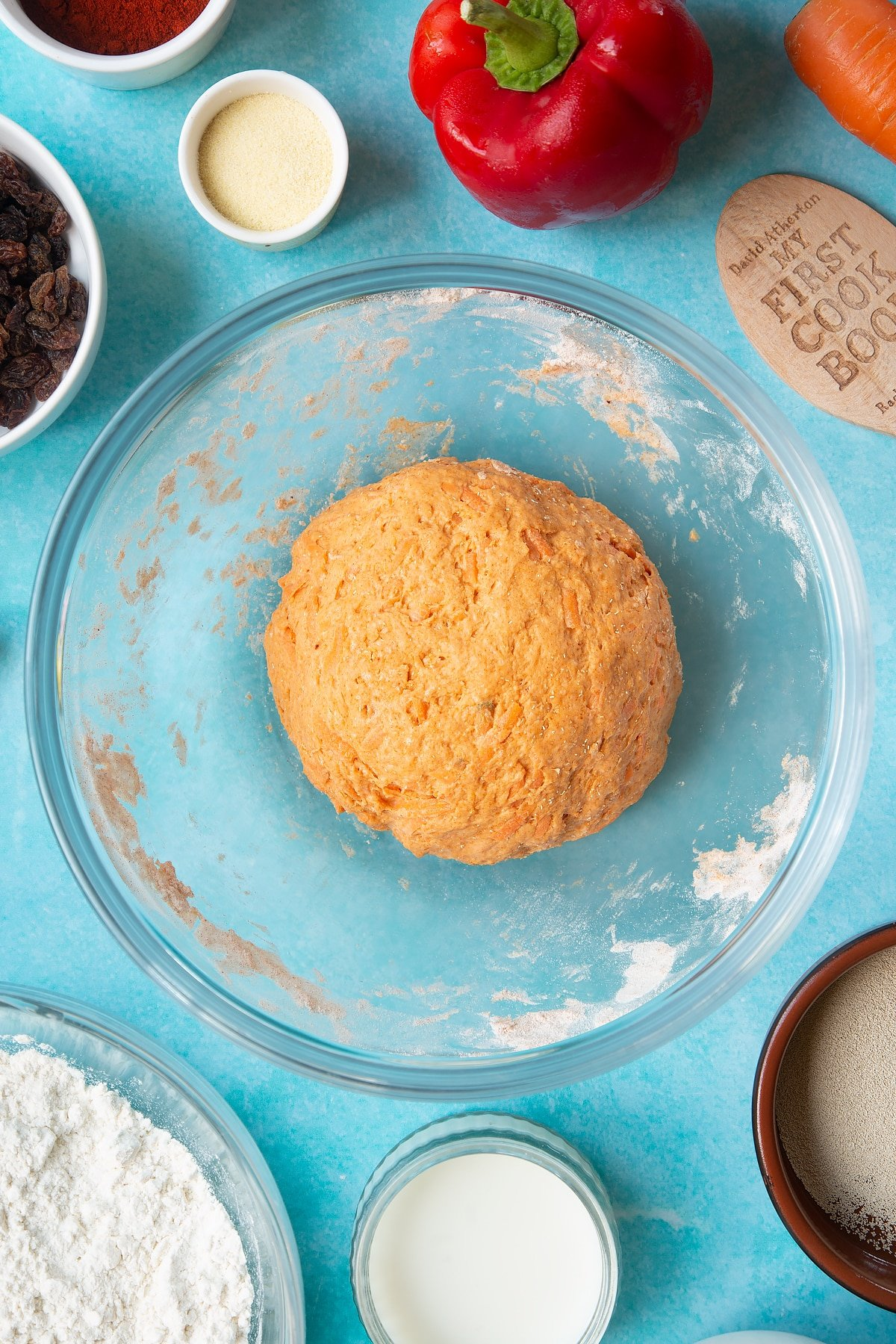Paprika and carrot bread dough, slightly proved in a mixing bowl. Ingredients to make bread snakes surround the bowl.