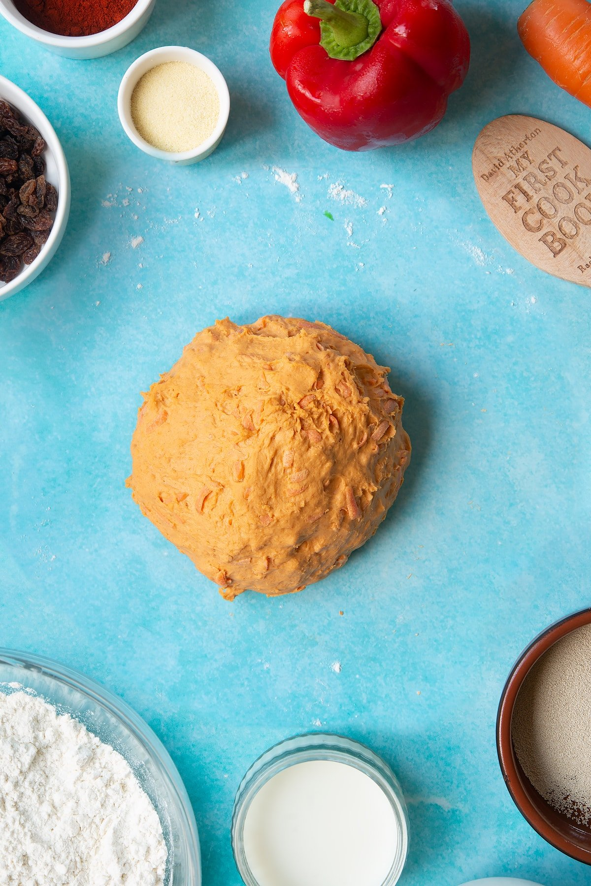 Paprika and carrot bread dough, freshly kneaded. Ingredient to make bread snakes surround the dough.