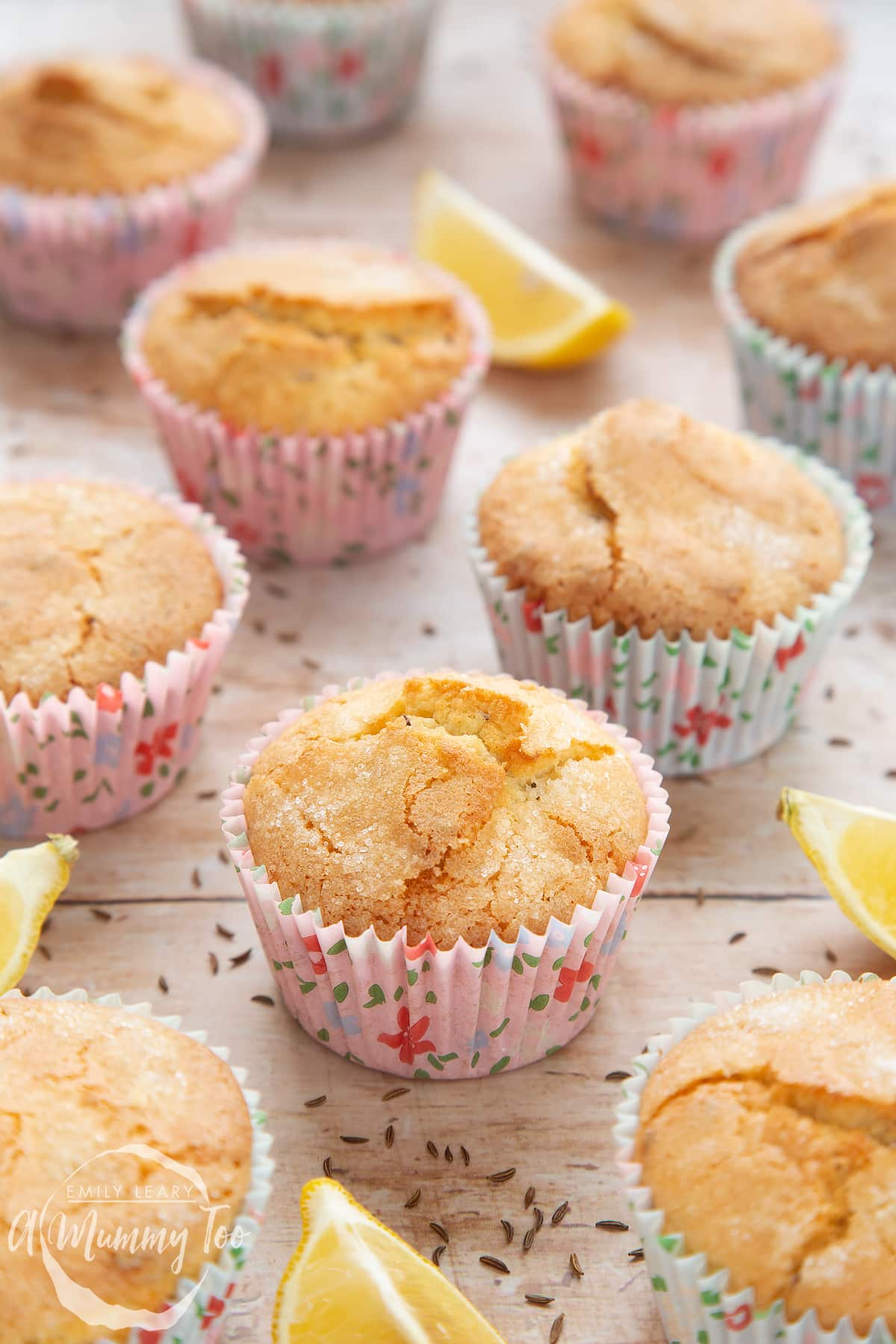 Front angle shot of caraway seed muffin with lemons in the side and a mummy too logo in the lower-left corner