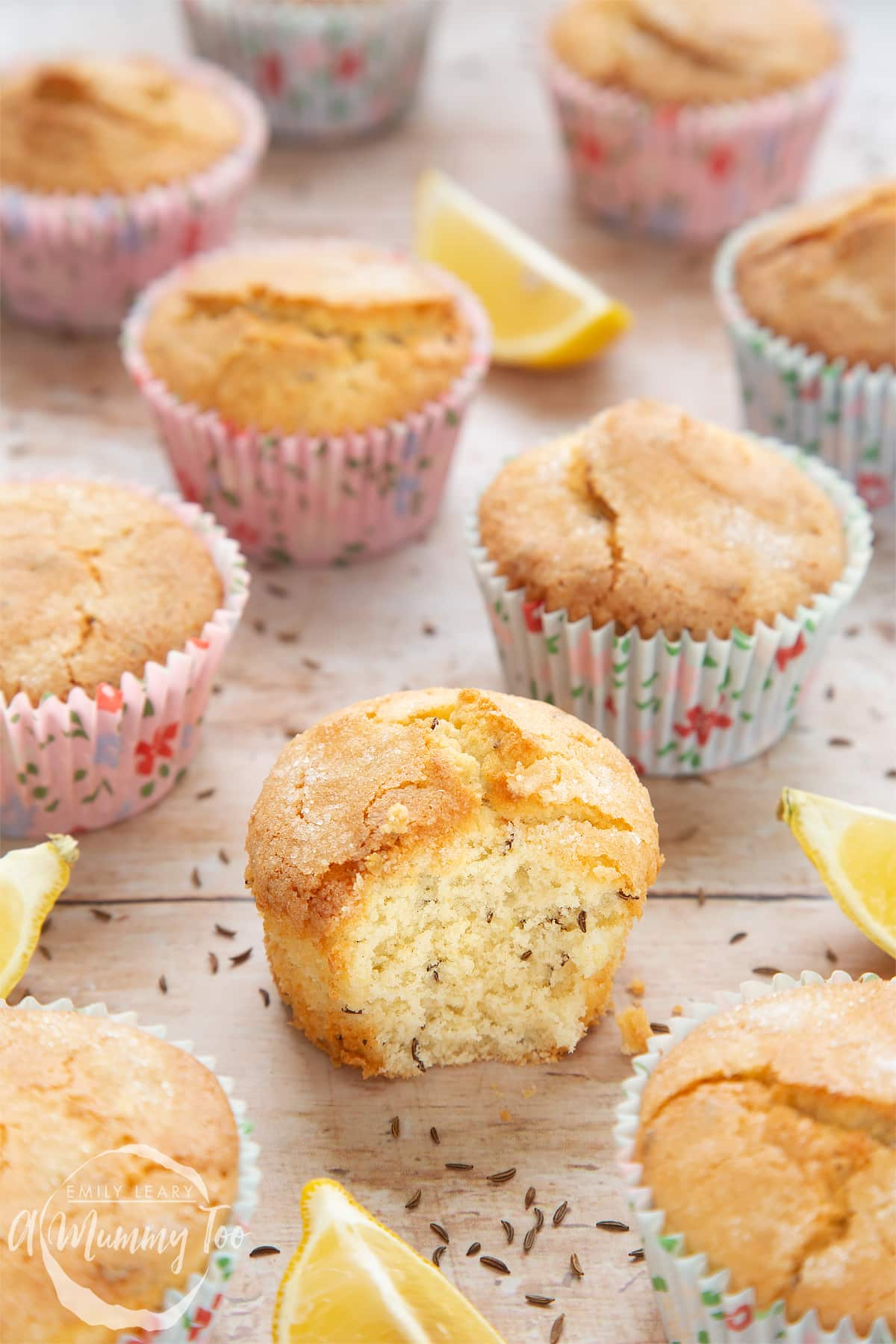 Front angle shot of Caraway seed muffin and lemons with a mummy too logo in the lower-left corner