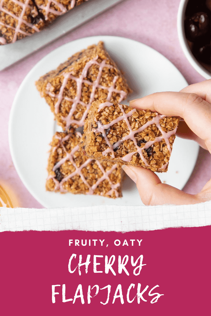 Overhead shot of a hand holding a cherry flapjack with graphic text FRUITY, OATY CHERRY FLAPJACKS below