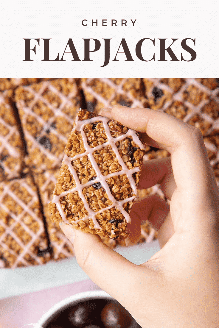 Graphic text step-by-step recipe CHERRY FLAPJACKS above overhead shot of a hand touching a cherry oat bar with website URL below