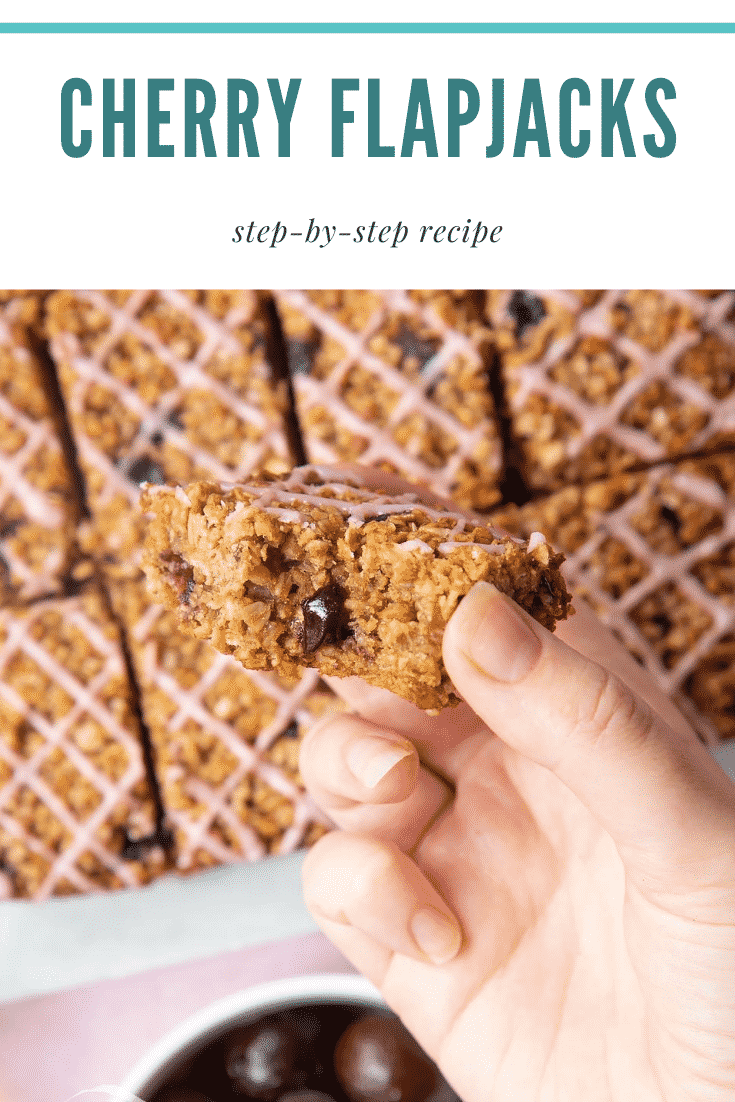 Graphic text STEP-BY-STEP RECIPE CHERRY FLAPJACKS EASY AND DELICIOUS above Overhead shot of a hand holding a cherry flapjack with a mummy too logo in the lower-left corner
