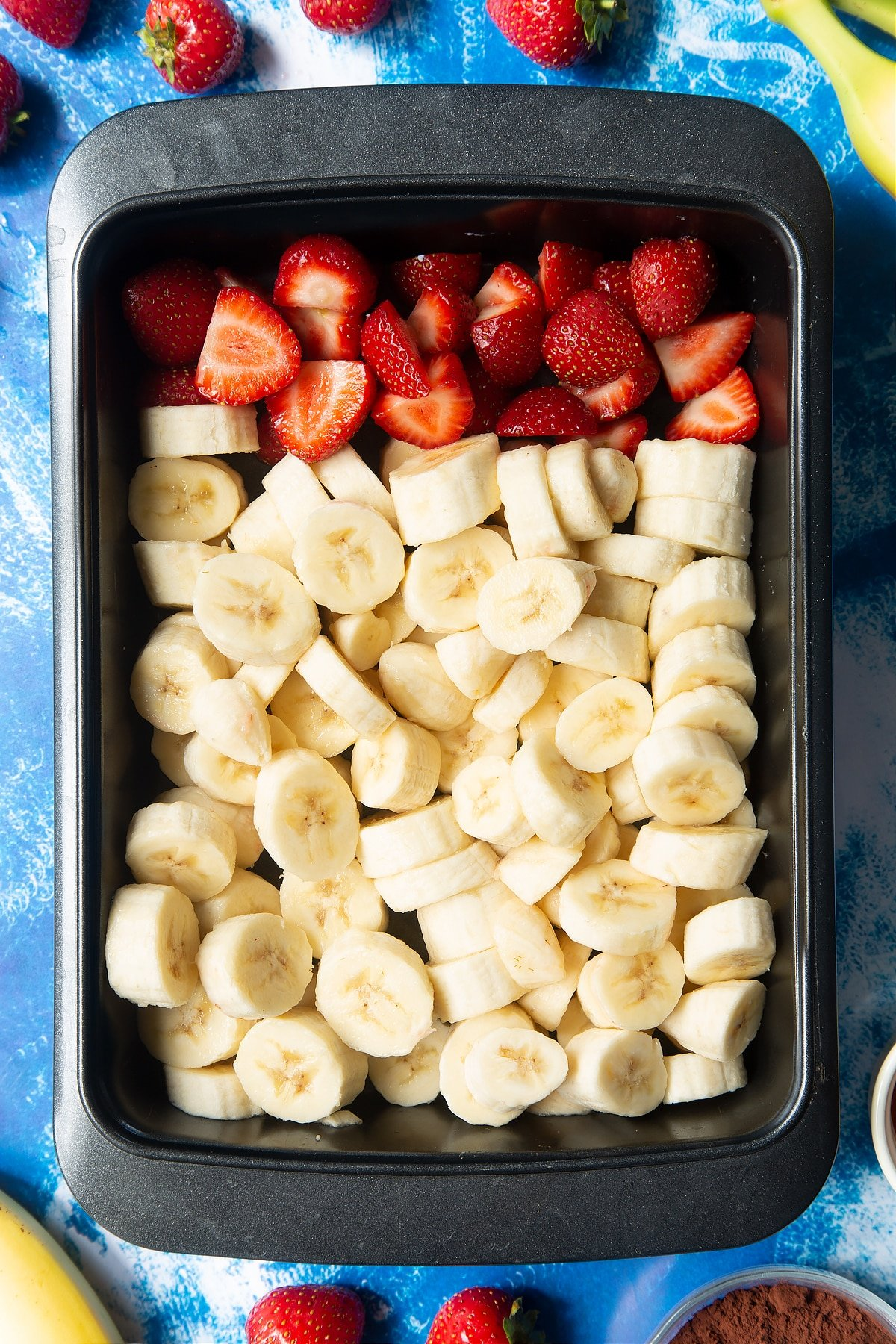 Sliced bananas and strawberries in a tray.