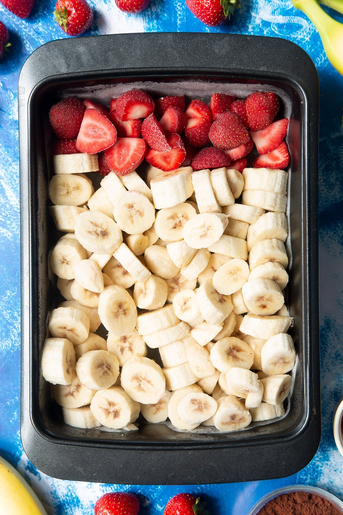 Frozen sliced bananas and strawberries in a tray.