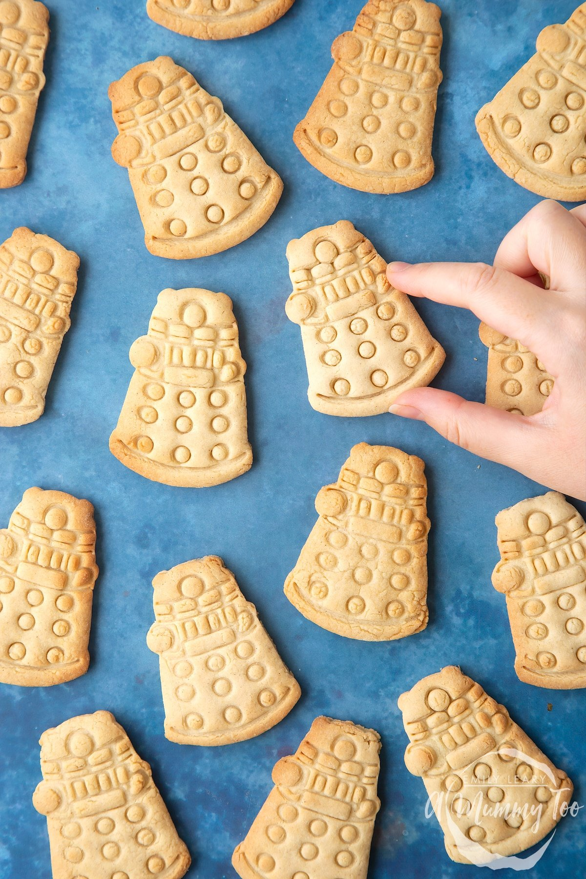 Dalek cookies on a blue background. The cookies are undecorated. A hand reaches to take one.