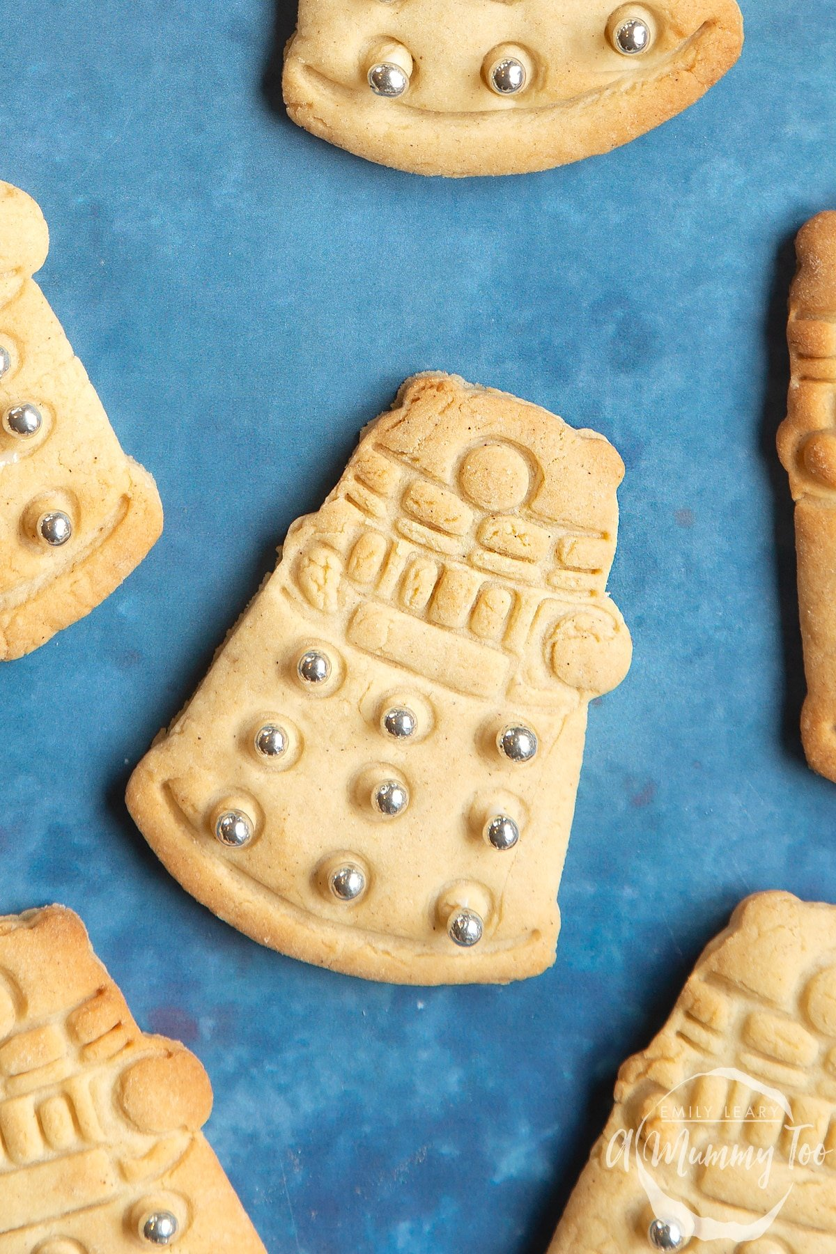 Close up of a Dalek cookies on a blue background. The cookie is decorated with edible silver candy balls.