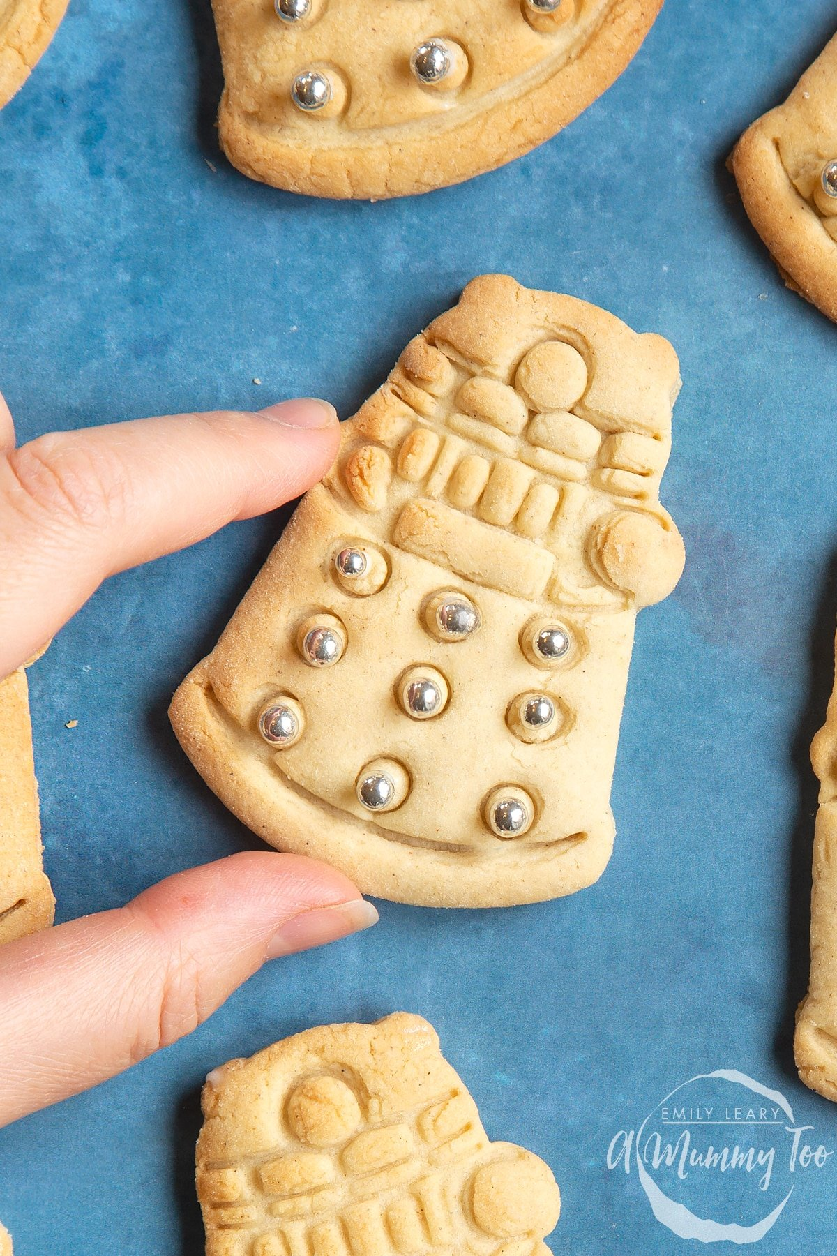 Close up of a Dalek cookies on a blue background. The cookie is decorated with edible silver candy balls. A hand reaches to take it.