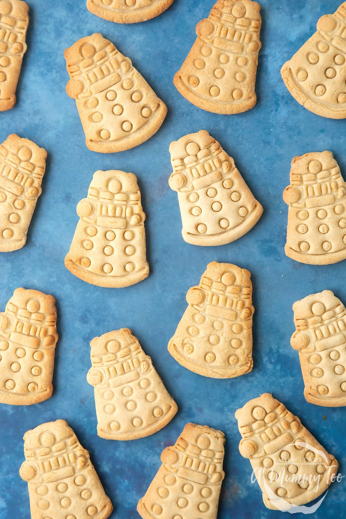 Dalek cookies on a blue background. The cookies are undecorated.