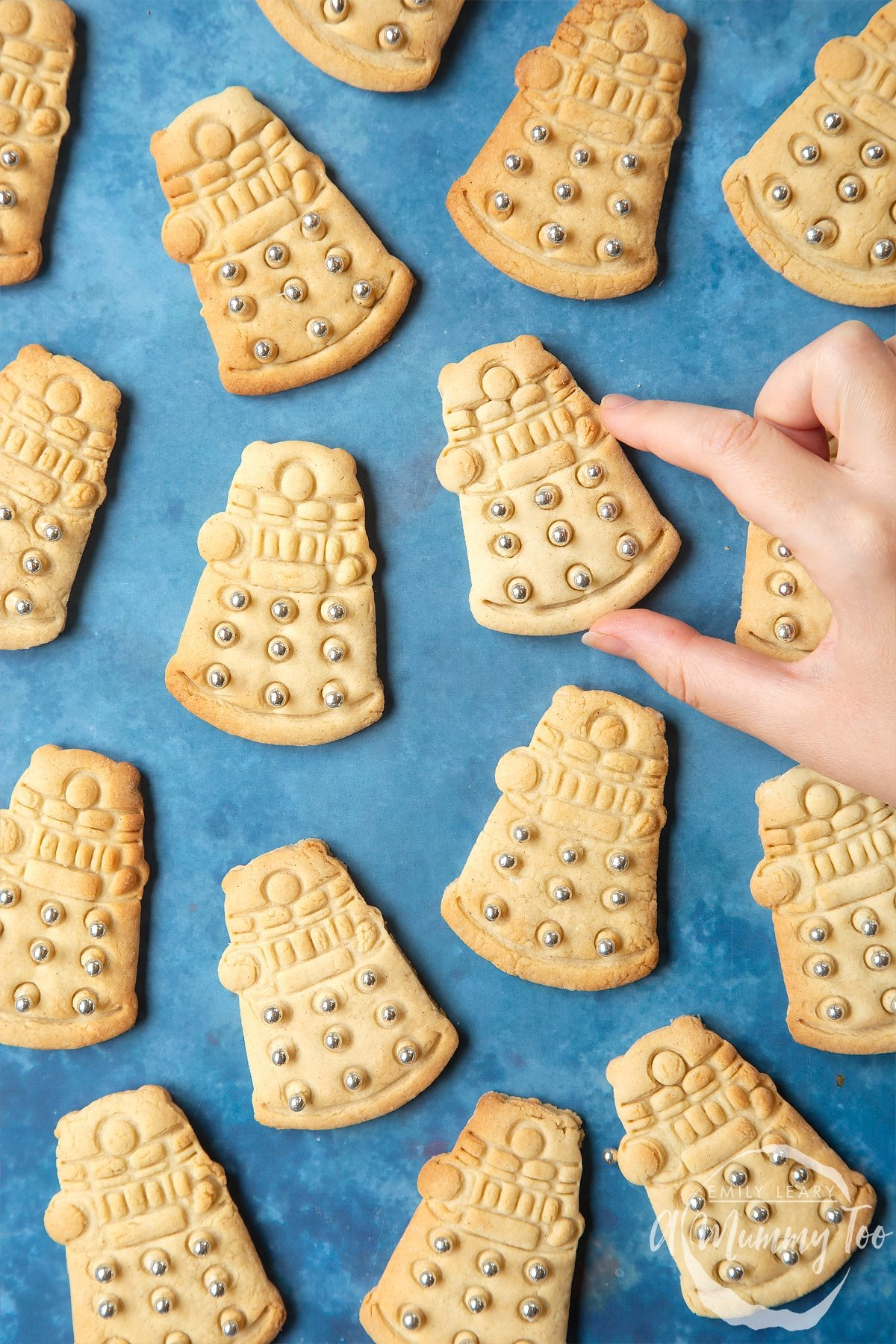 Dalek sugar cookies decorated with silver candy balls. A hand reaches for one.