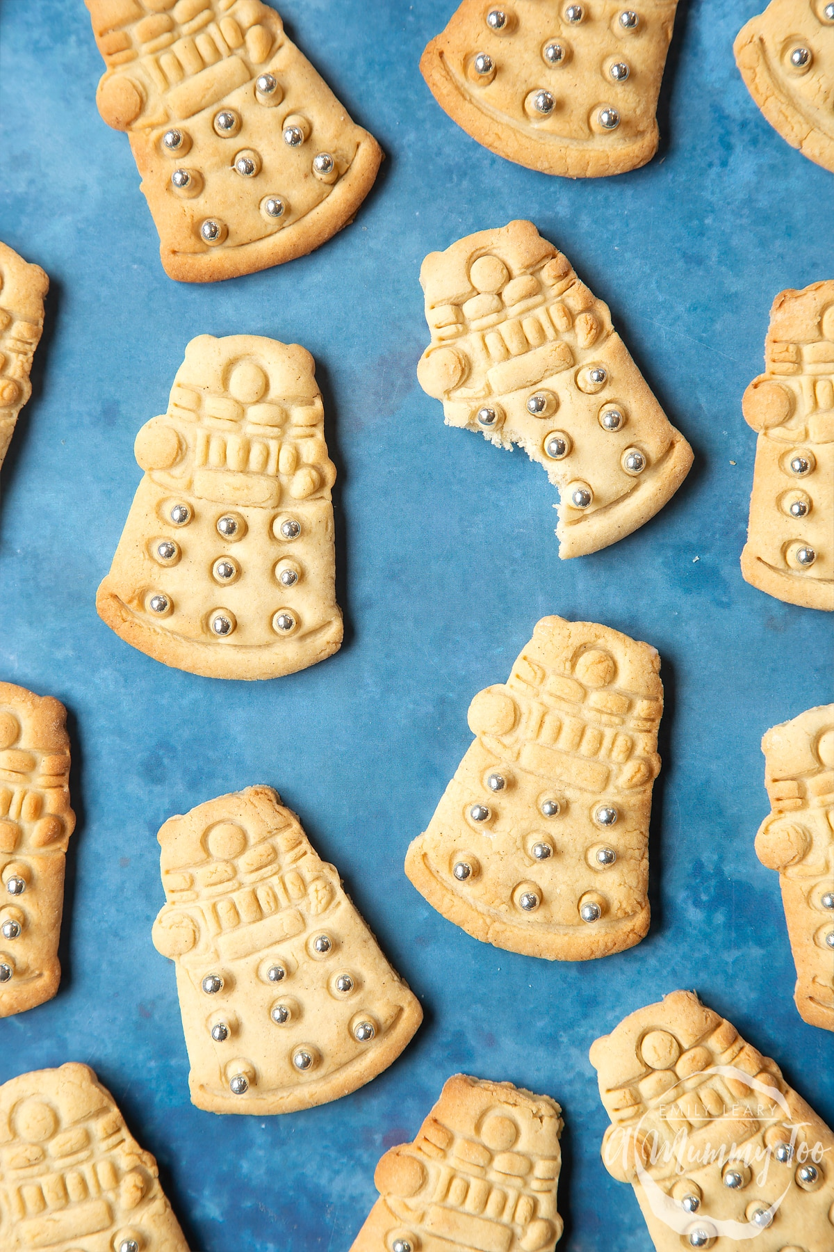Dalek cookies on a blue background. The cookies are decorated with edible silver candy balls. One of the cookies has a bite out of it.