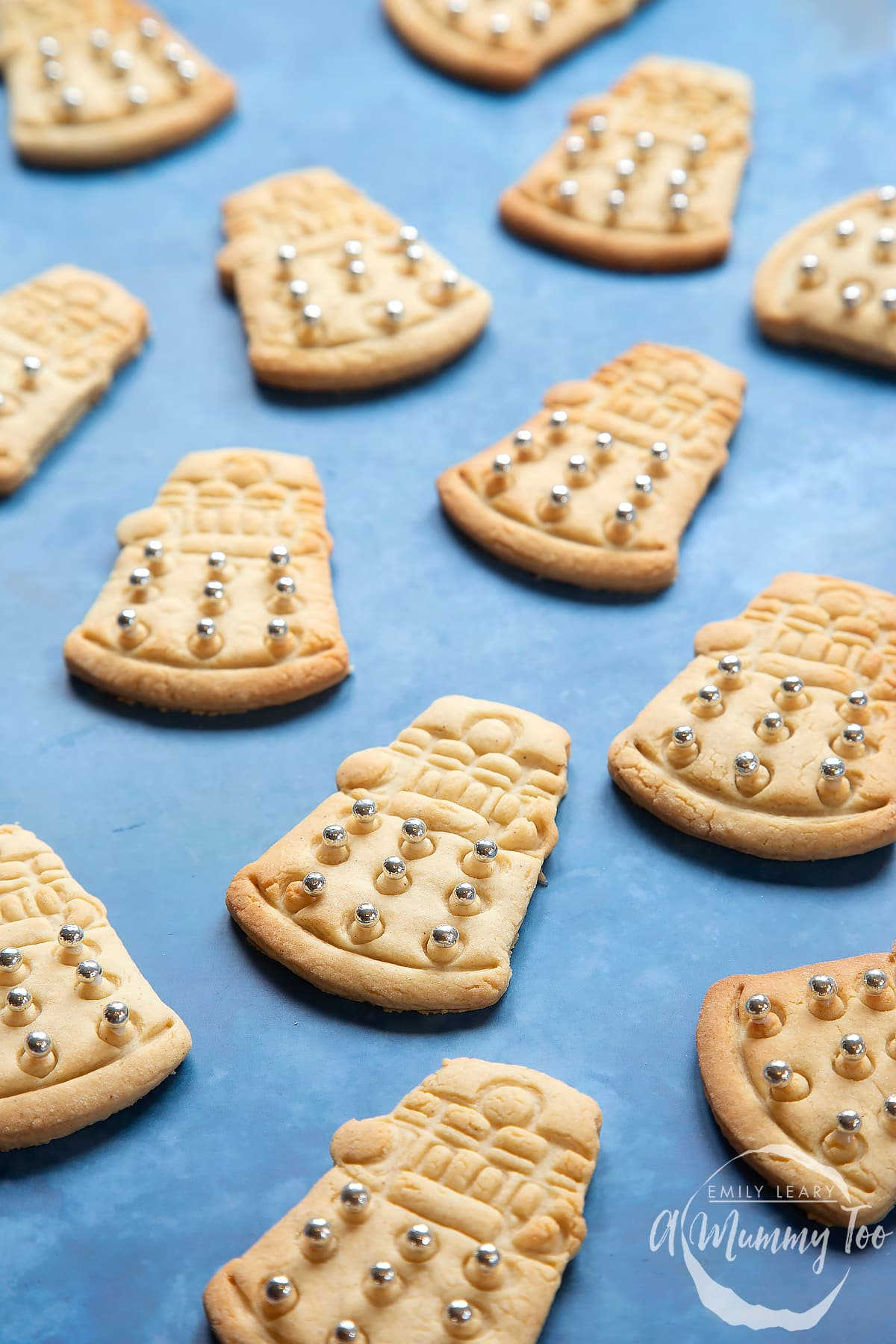 Dalek cookies on a blue background. The cookies are decorated with edible silver candy balls adhered with white icing.
