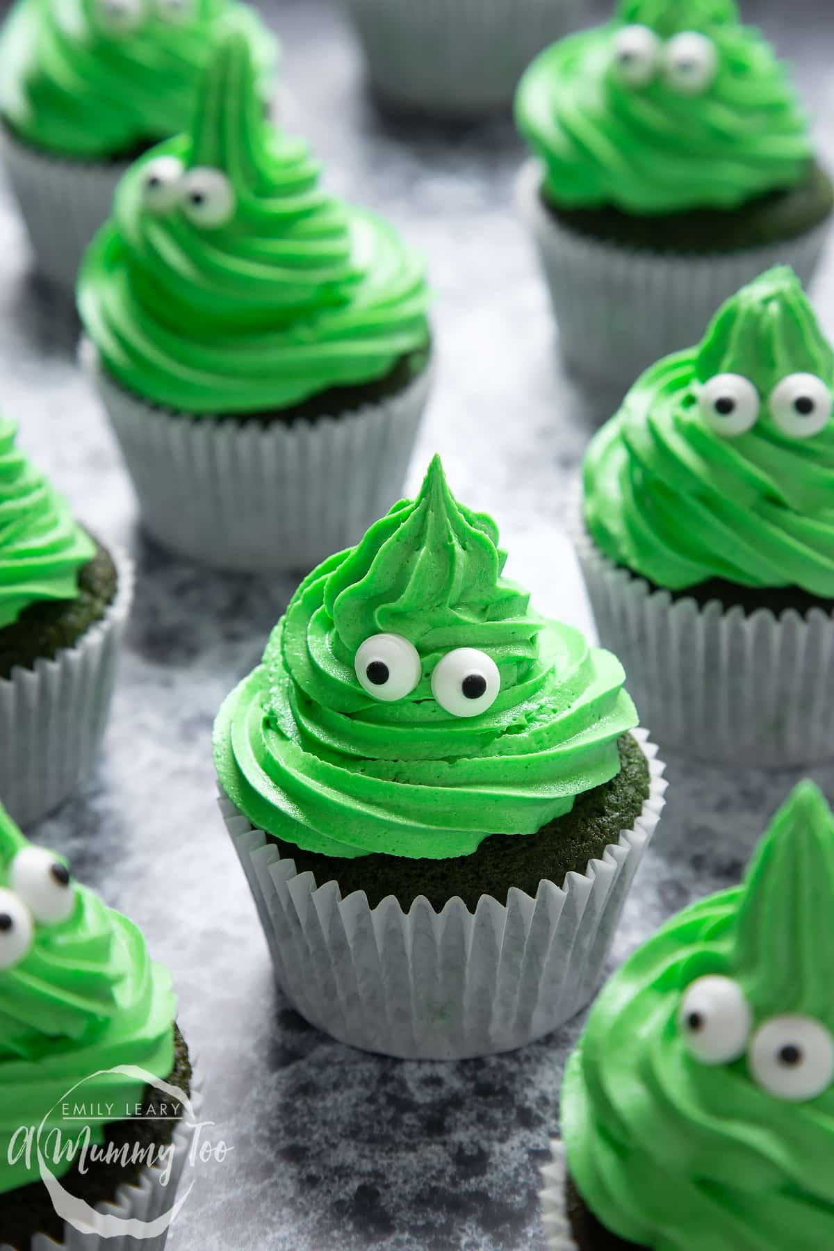 Green monster cakes made with dyed-green chocolate chip cupcakes topped with green peppermint frosting with added candy eyes.