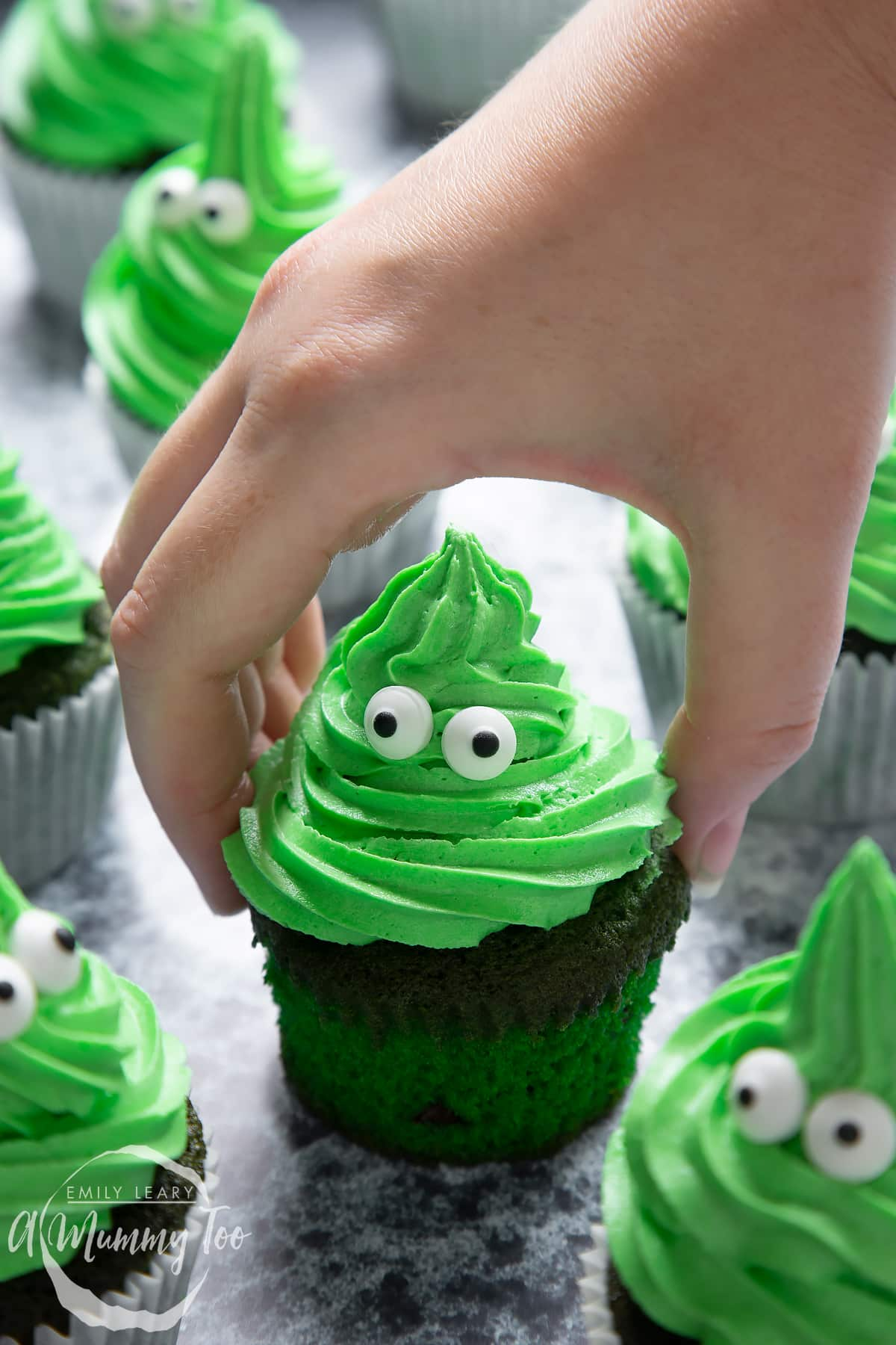 Green monster cakes made with dyed-green chocolate chip cupcakes topped with green peppermint frosting with added candy eyes. A hand reaches for one.