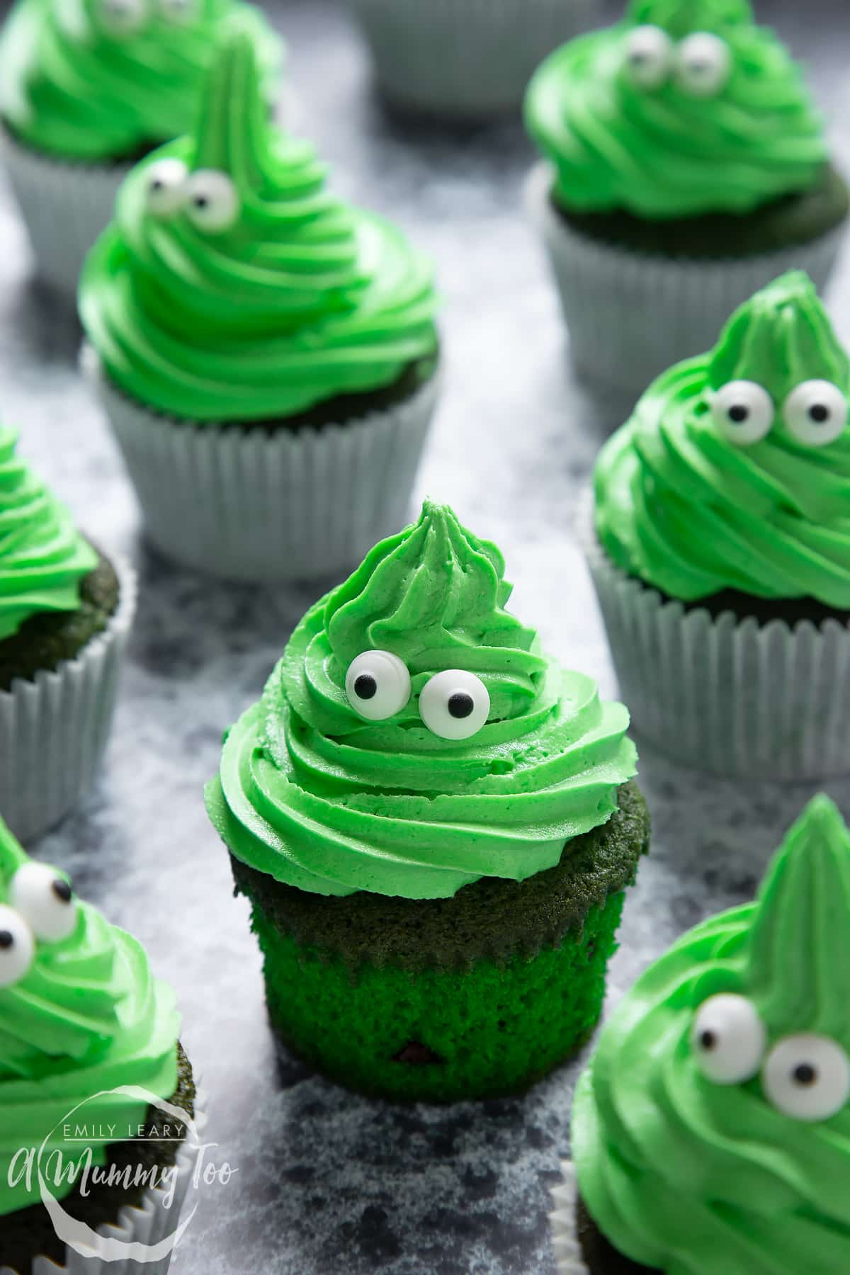 Green monster cakes made with dyed-green chocolate chip cupcakes topped with green peppermint frosting with added candy eyes. One has been unwrapped.