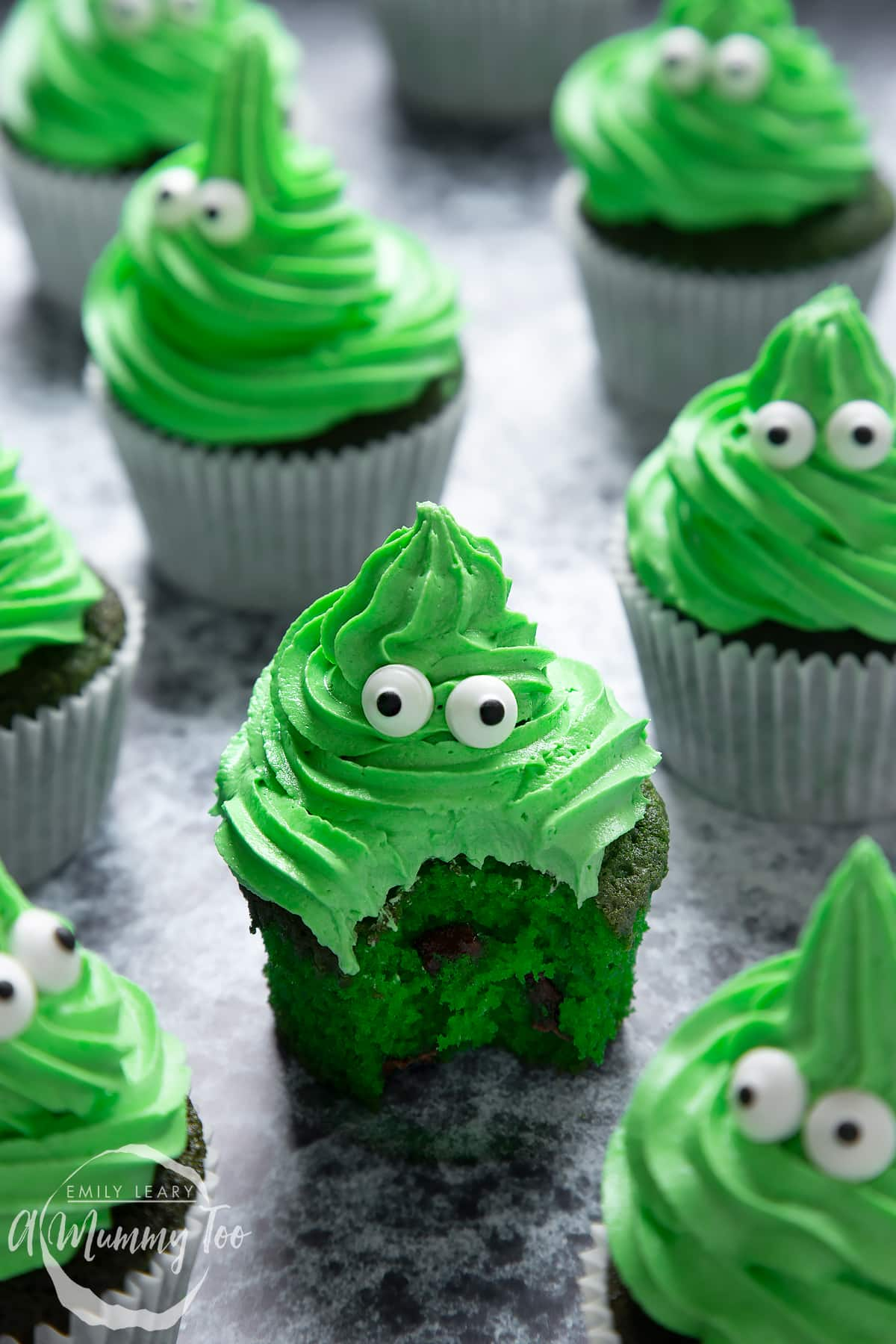 Green monster cakes made with dyed-green chocolate chip cupcakes topped with green peppermint frosting with added candy eyes. One has been bitten open.