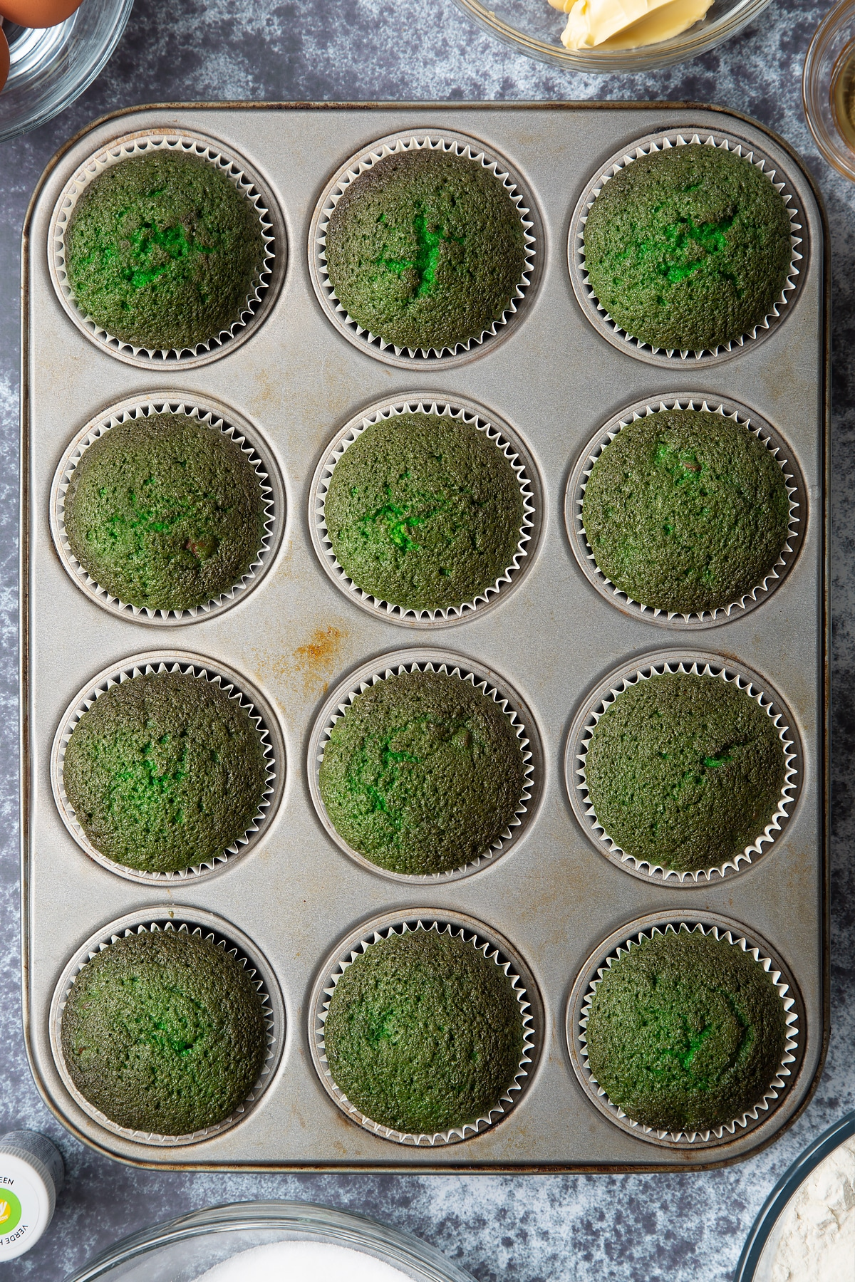 Cooked green vanilla chocolate chip cupcakes in a 12 hole muffin tray. Ingredients to make green monster cakes surround the tray.