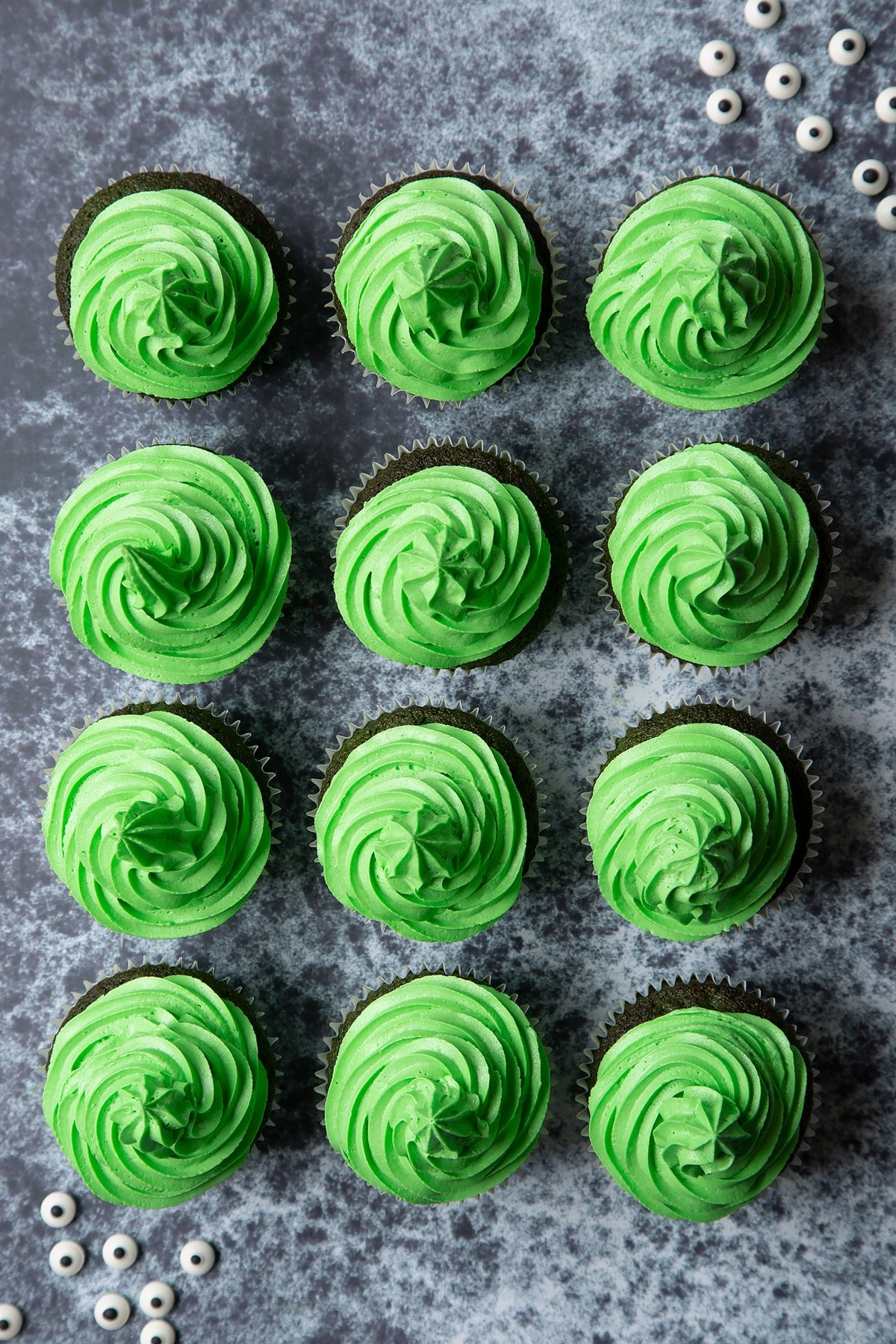 Green vanilla chocolate chip cupcakes decorated with swirls of green peppermint frosting.