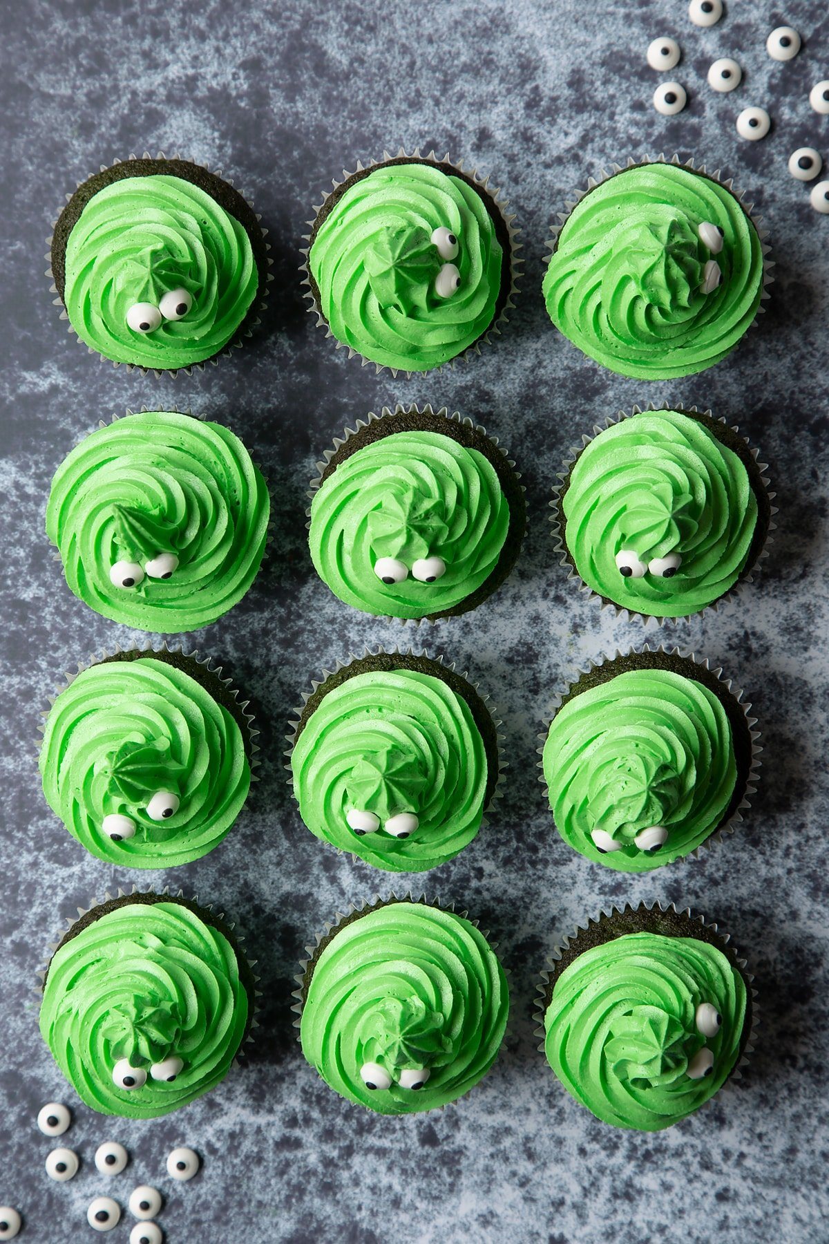 Green vanilla chocolate chip cupcakes decorated with swirls of green peppermint frosting and candy eyeballs to look like green monster cakes.