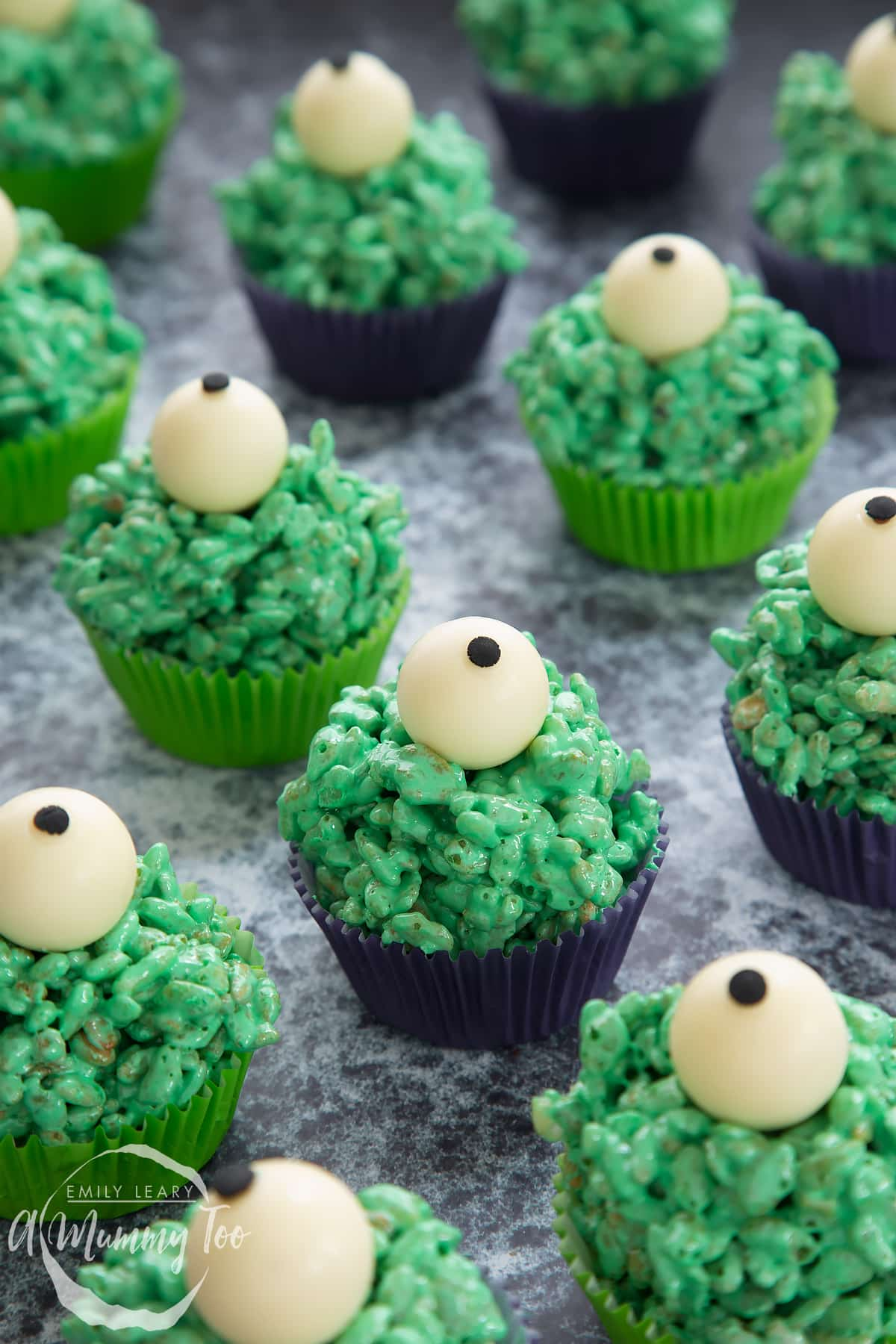 Halloween crispy cakes in purple and green cupcake cases. The crispy cakes are dyed green and topped with white chocolate spheres decorated to look like eyeballs.