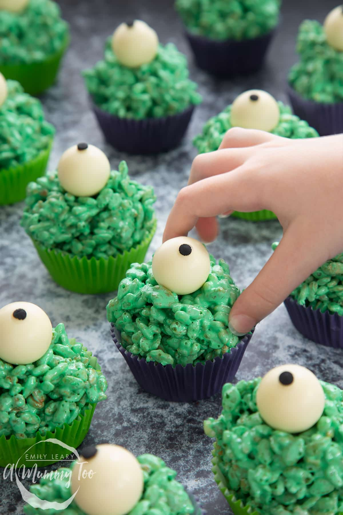 Halloween crispy cakes in purple and green cupcake cases. The crispy cakes are dyed green and topped with white chocolate spheres decorated to look like eyeballs. A little hand reaches for one.