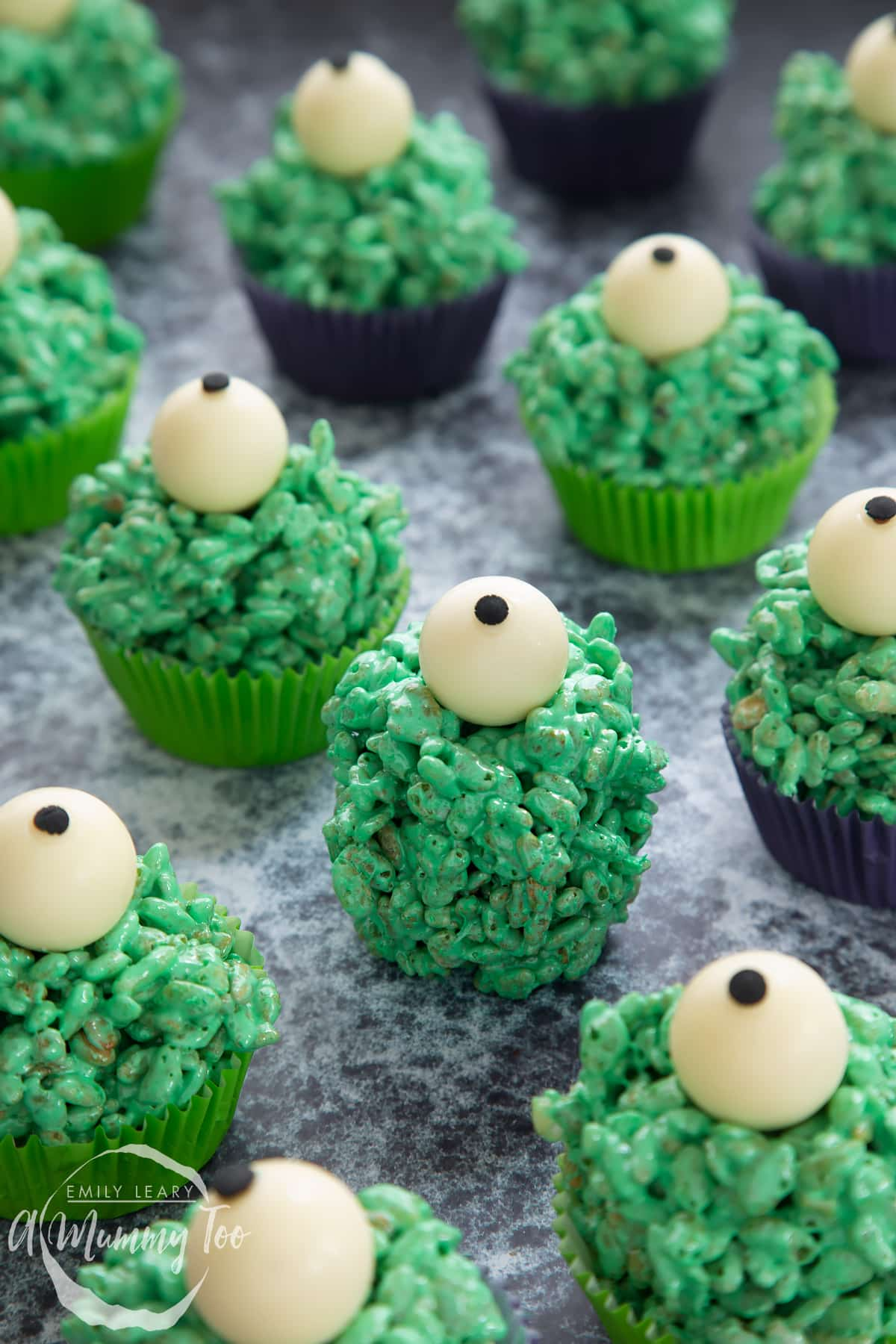 Halloween crispy cakes in purple and green cupcake cases. The crispy cakes are dyed green and topped with white chocolate spheres decorated to look like eyeballs. One has been unwrapped.