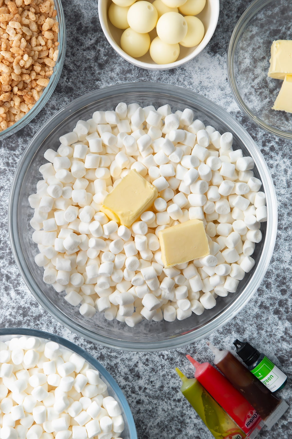 Mini marshmallows and cubes of butter in a large mixing bowl. Ingredients to make Halloween crispy cakes surround the bowl.