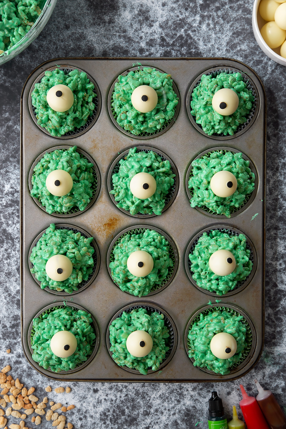12-hole muffin tray lined with cupcake cases filled with green rice crispy treats topped with white chocolate spheres decorated with icing pupils. Ingredients to make Halloween crispy cakes surround the tray.