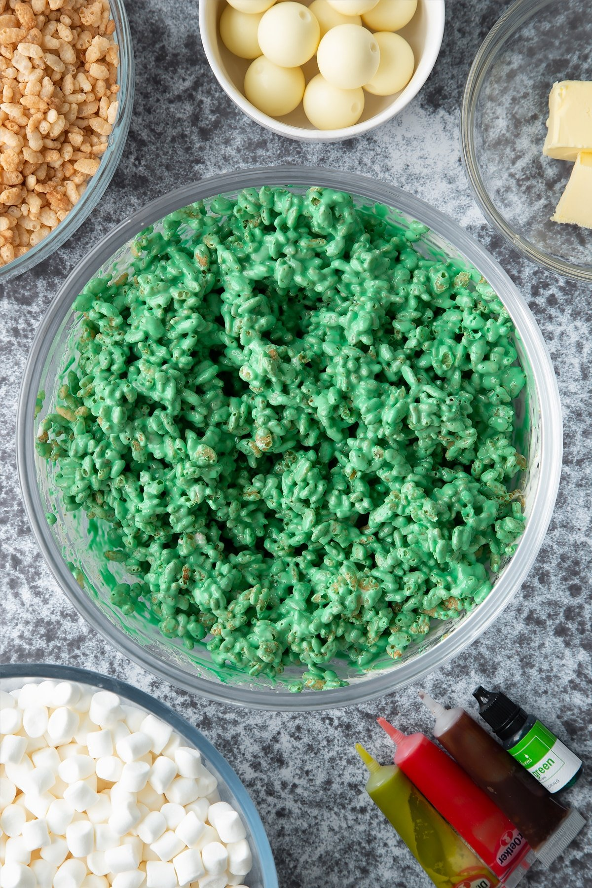 Dyed-green rice crispie treat mix in a large mixing bowl. Ingredients to make Halloween crispy cakes surround the bowl.