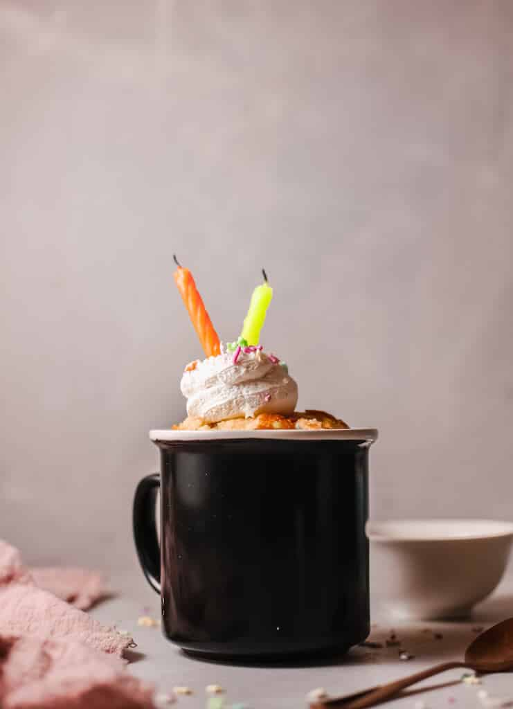 Funfetti birthday cake in a black mug, topped with a swirl of frosting, sprinkles and two candles.