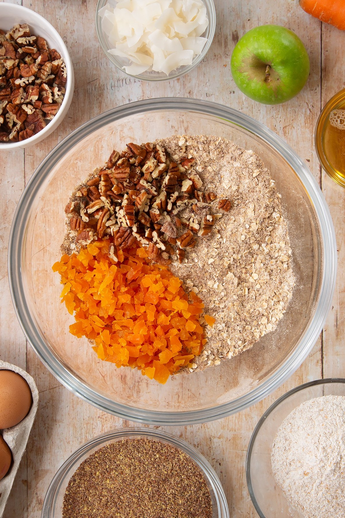 Overhead shot of dry ingredients mix, dried apricots and nuts in a large clear bowl