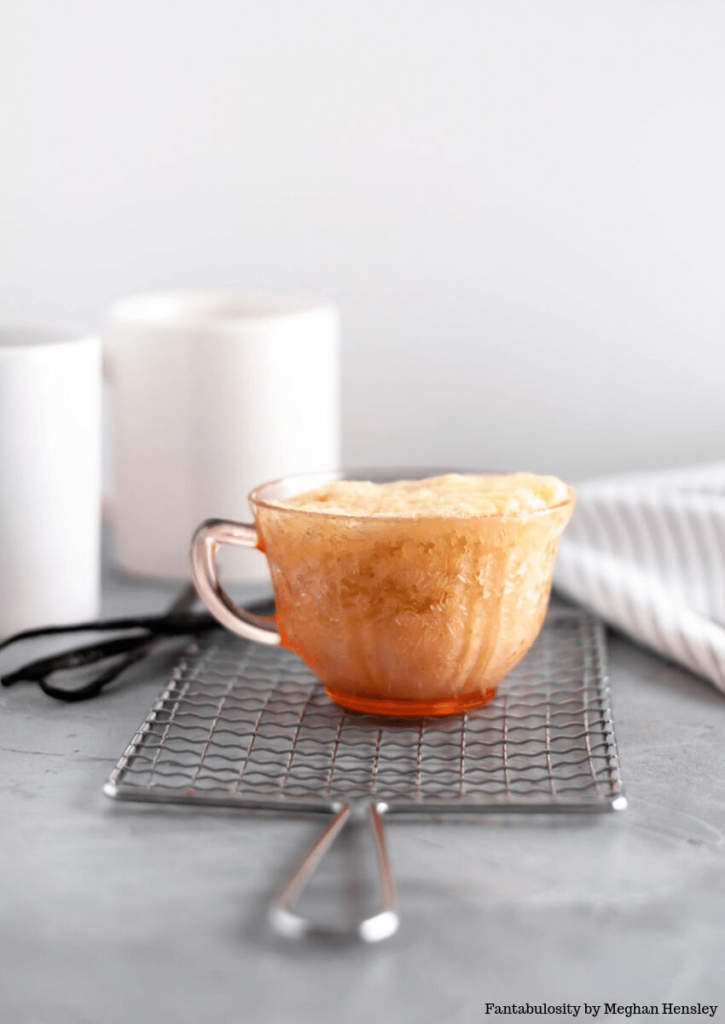 Vanilla mug cake, made in a transparent teacup, standing on a small cooling rack.
