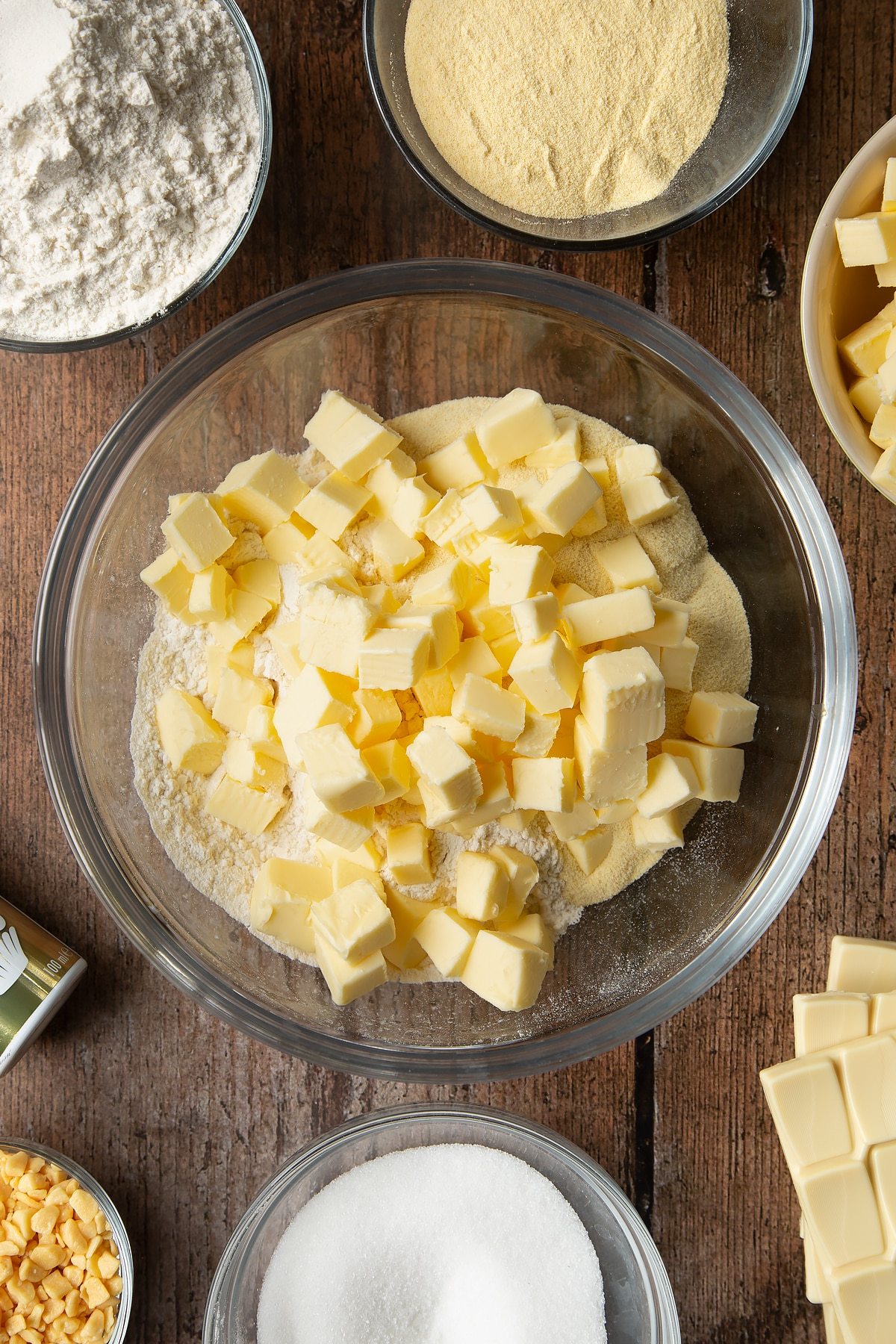 Overhead shot of cold, cubed butter and dry ingredients in a large clear bowl