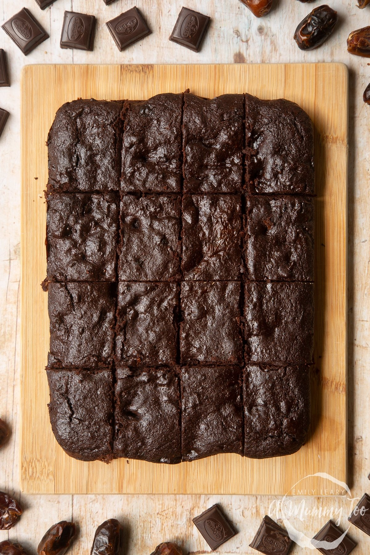 16 whole grain brownies made with dates and dark chocolate arranged on a pale wooden board.