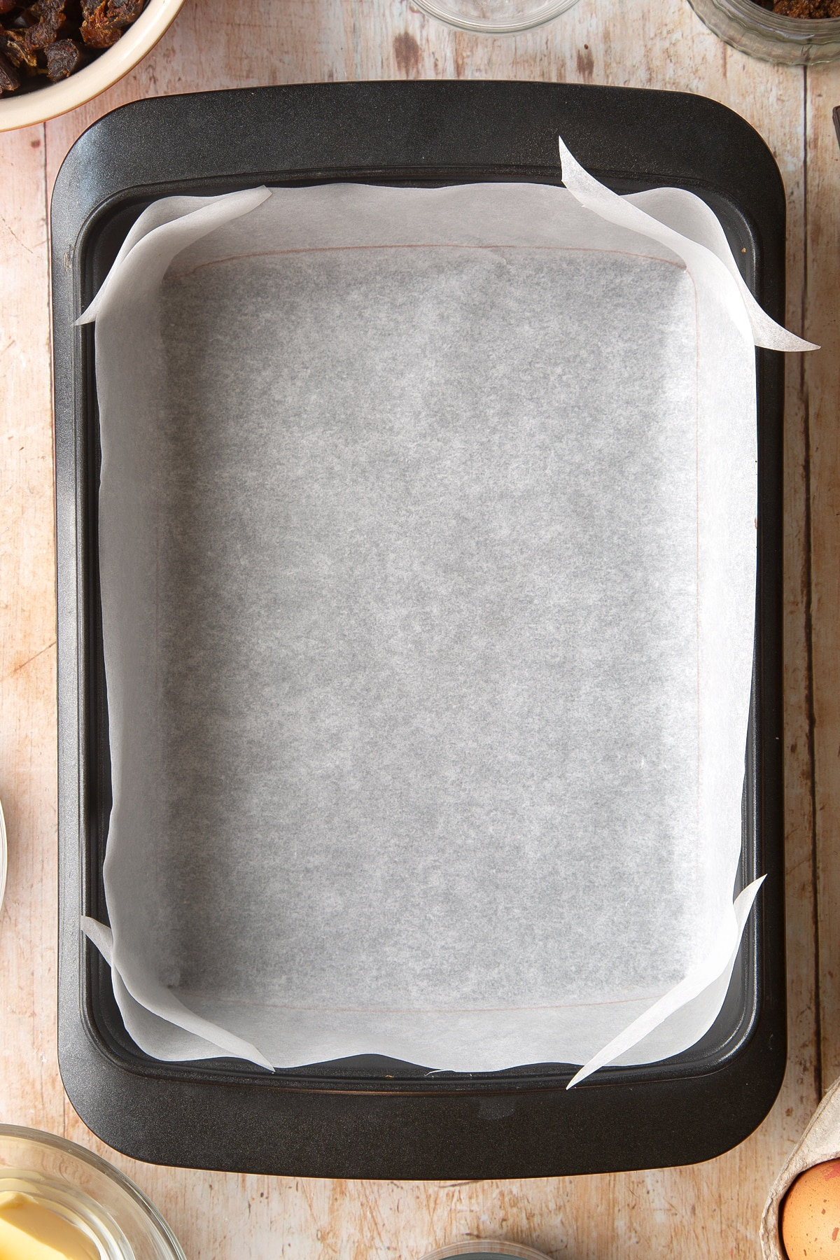 A rectangular tin lined with baking paper. Ingredients to make whole grain brownies surround the tin.