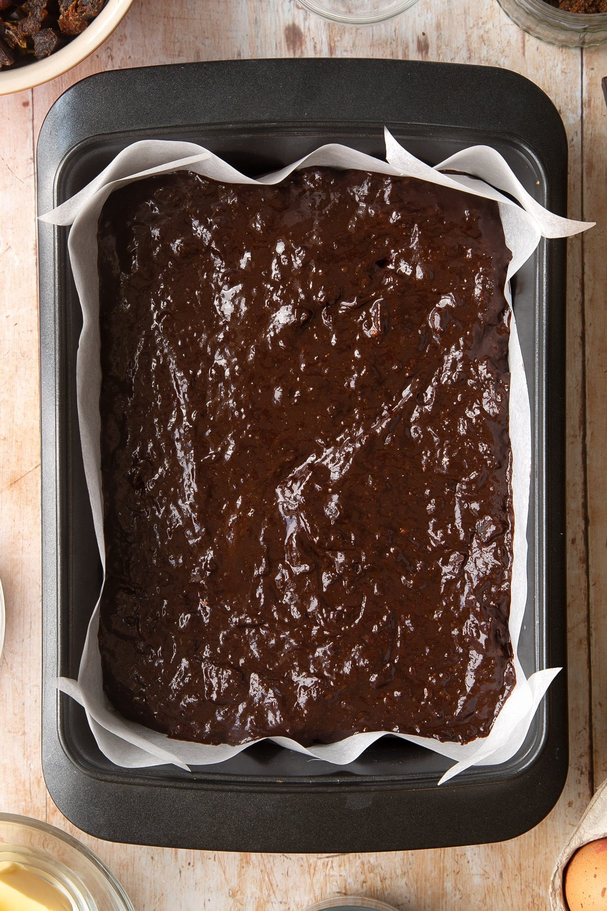 A rectangular tin lined with baking paper and filled with whole grain brownie batter. Ingredients to make whole grain brownies surround the tin.