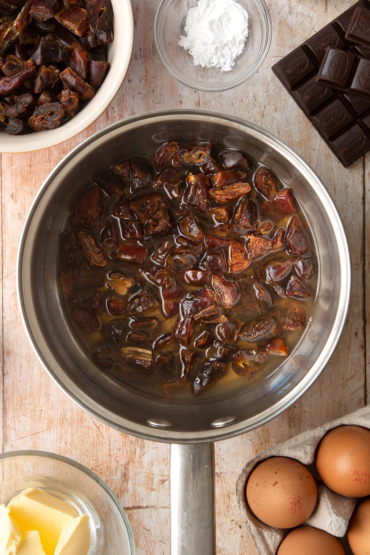 A sauce pan containing chopped dried dates and water. Ingredients to make whole grain brownies surround the pan.