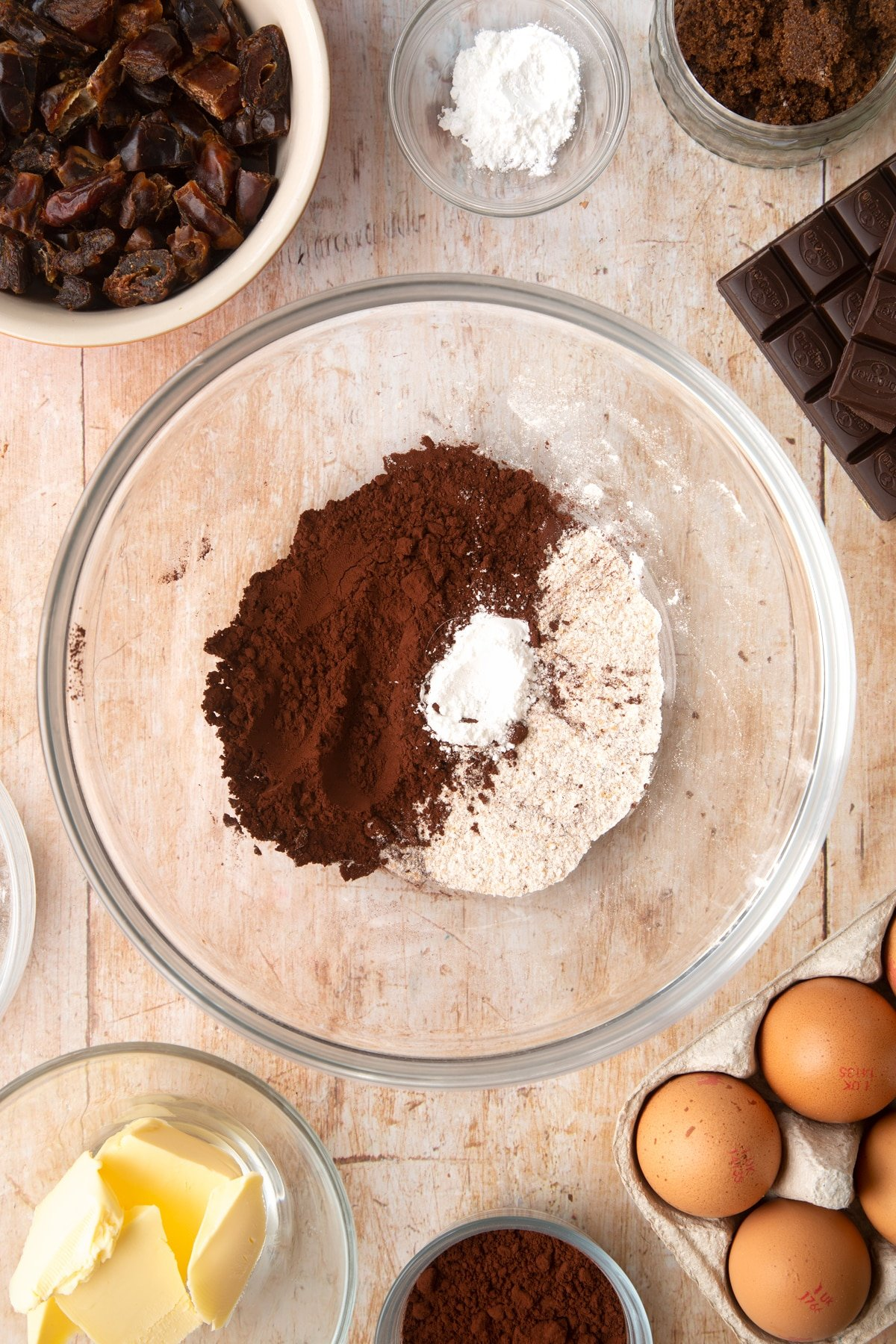 A mixing bowl containing cocoa, wholemeal flour and baking powder. Ingredients to make whole grain brownies surround the bowl.