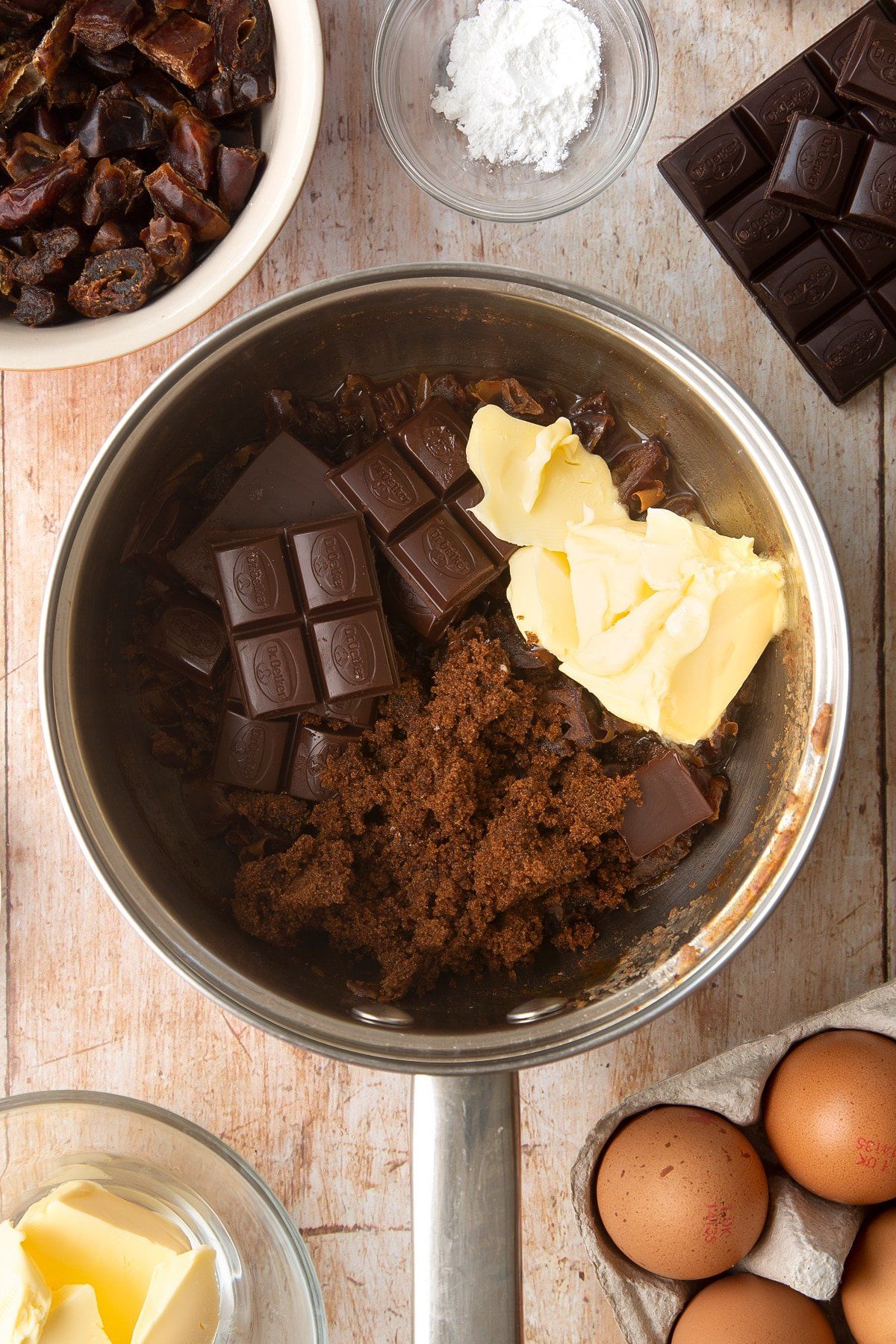 A sauce pan containing chopped dried dates simmered in water. On top sits butter, dark chocolate and sugar. Ingredients to make whole grain brownies surround the pan.