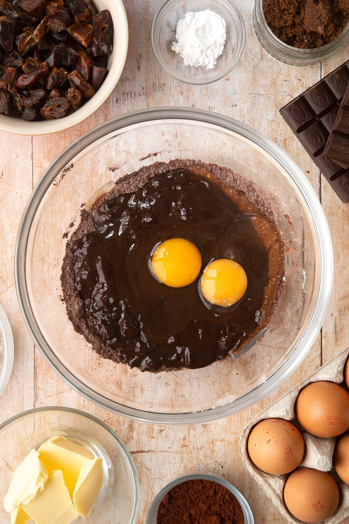 A mixing bowl containing cocoa, wholemeal flour and baking powder. The melted chocolate mixture and eggs have been added on top. Ingredients to make whole grain brownies surround the bowl.