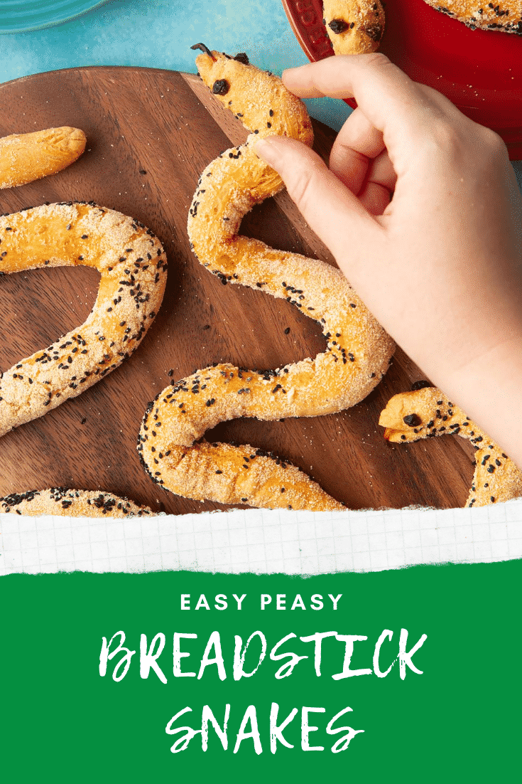 Bread snakes on a wooden board. A hand reaches for one. Caption reads: Easy peasy breadstick snakes.