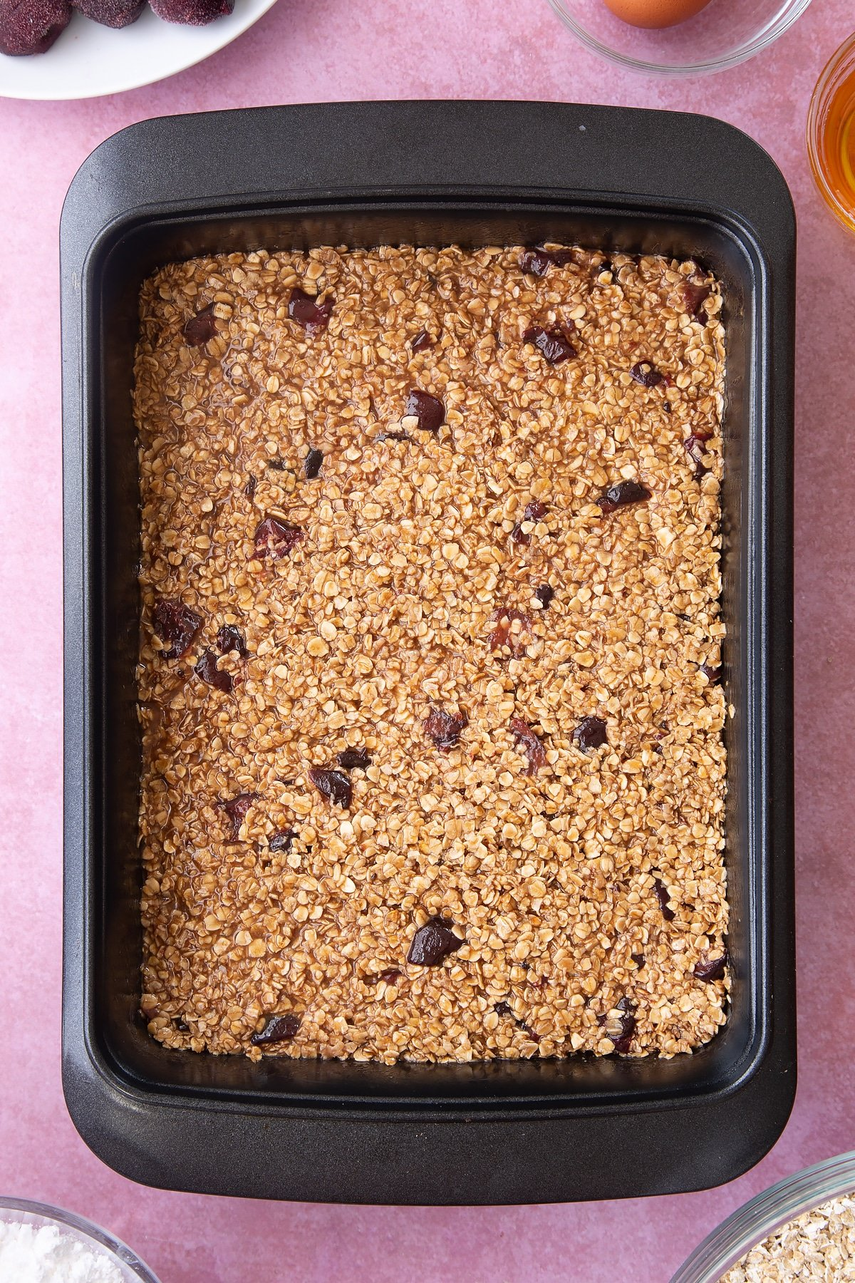 Overhead shot of flattened oats mix in a black baking tin