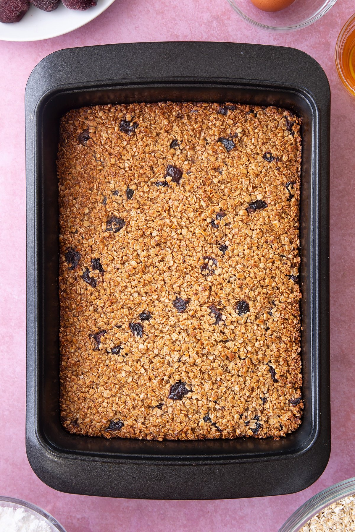 Overhead shot of cherry flapjacks in a black baking tin