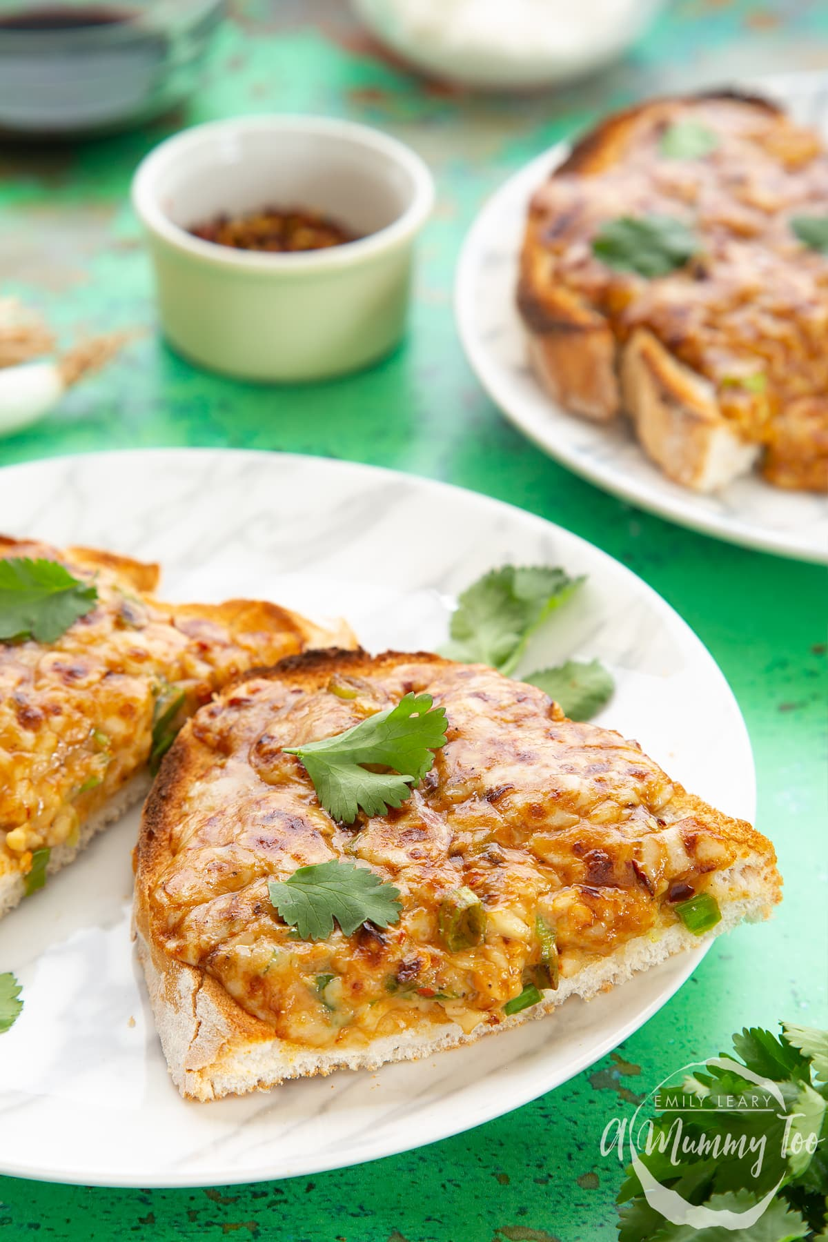 Two pieces of chilli cheese toast  on a white marbled plate, scattered with coriander.