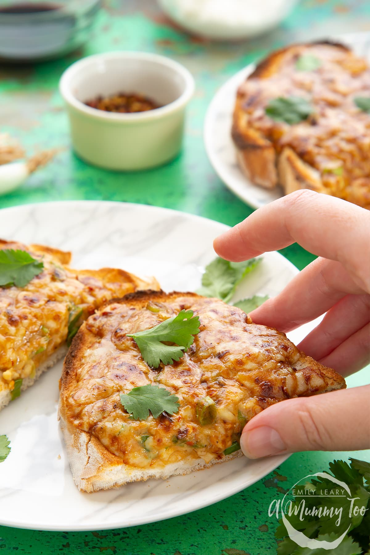 Two pieces of chilli cheese toast  on a white marbled plate, scattered with coriander. A hand reaches to take a piece.