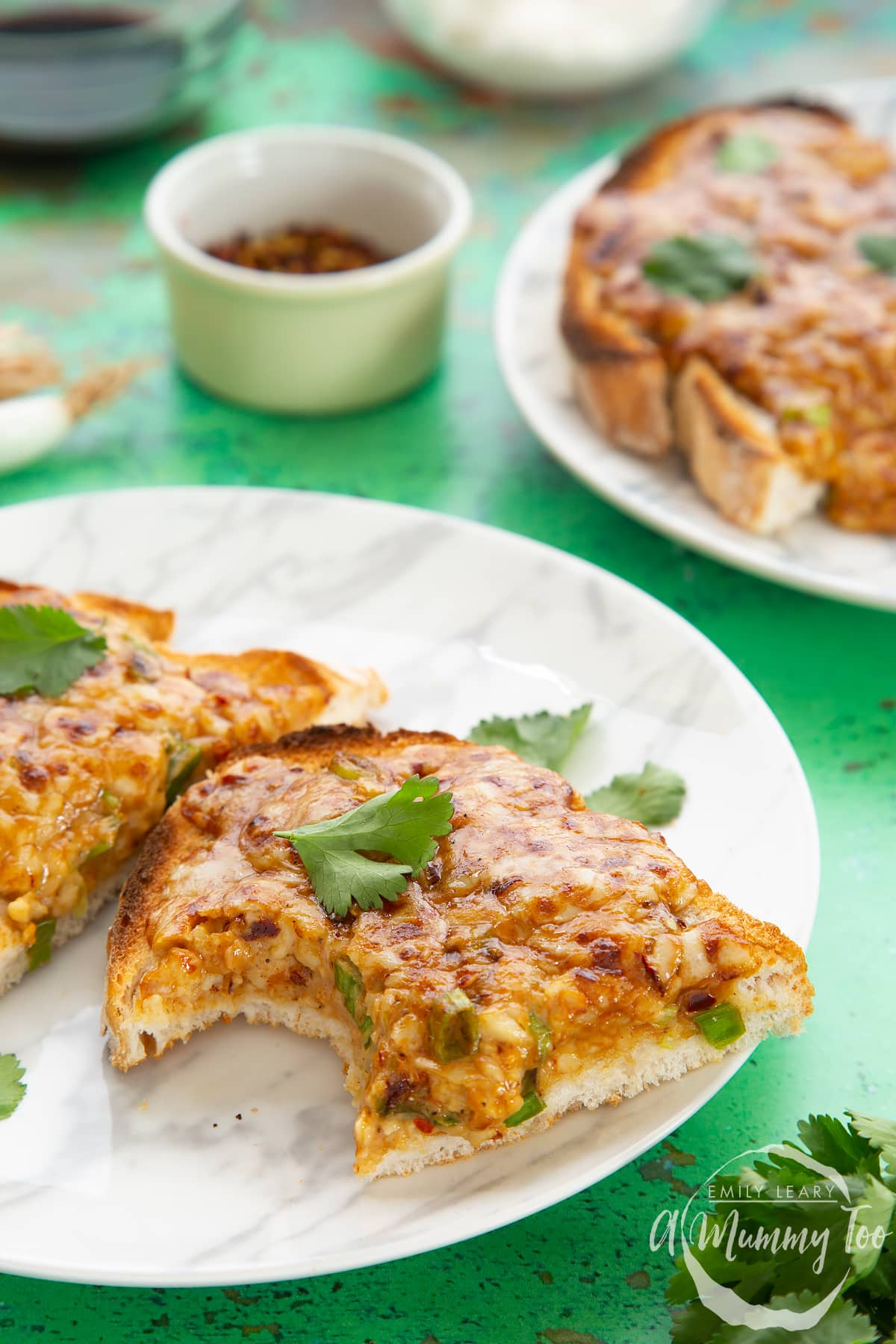 Two pieces of chilli cheese toast  on a white marbled plate, scattered with coriander. The piece in the foreground has a bite taken out of it.