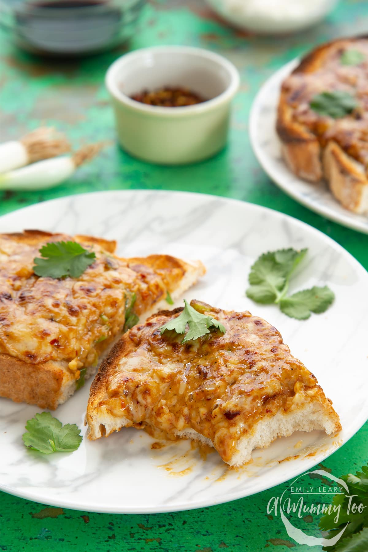 Two pieces of chilli cheese toast  on a white marbled plate, scattered with coriander. The piece in the foreground has several bites taken out of it.