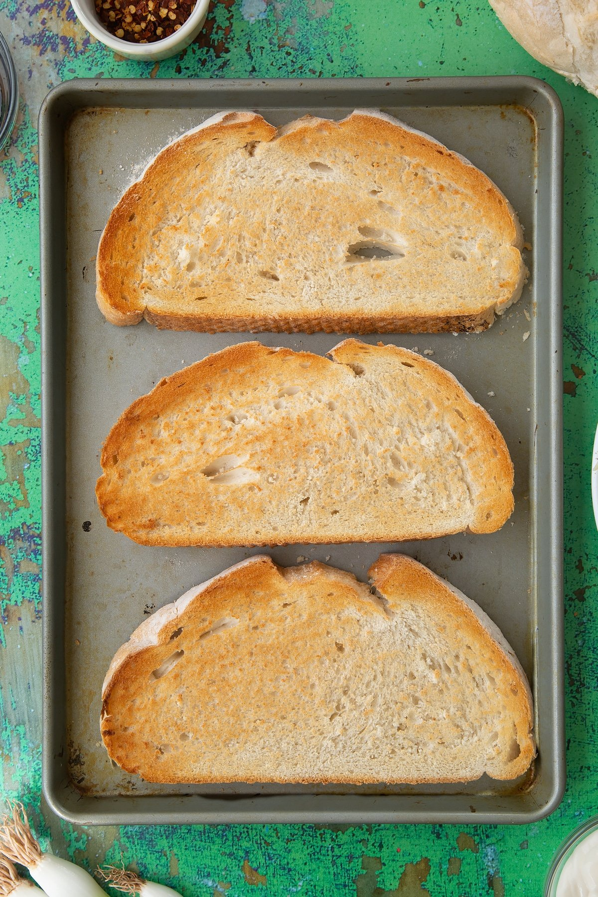 Three large slices of toast on a baking tray. Ingredients to make chilli cheese toast surround the tray.