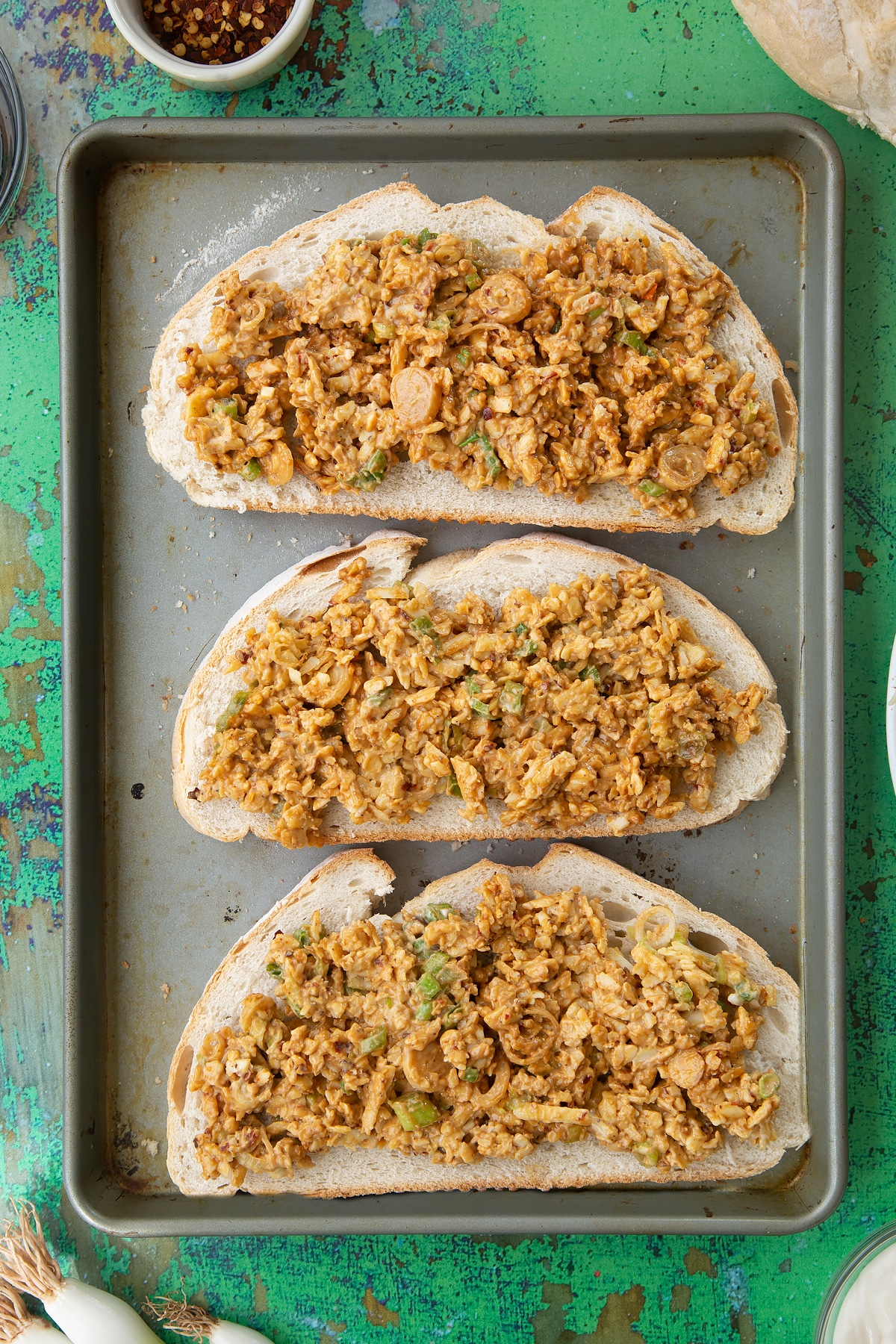 Three large slices of toast on a baking tray, spread with a mix of cheese, mayo and chilli. Ingredients to make chilli cheese toast surround the tray.